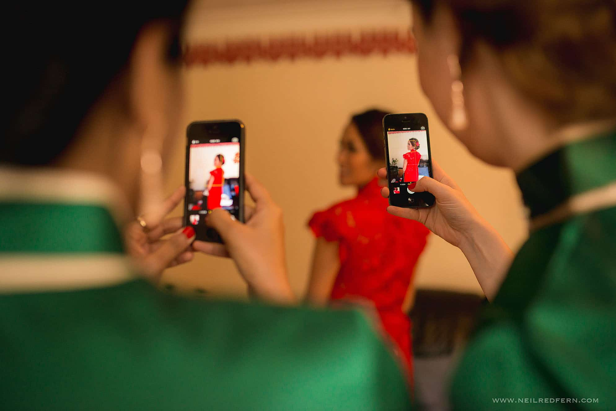 wedding guests taking photographs on phones