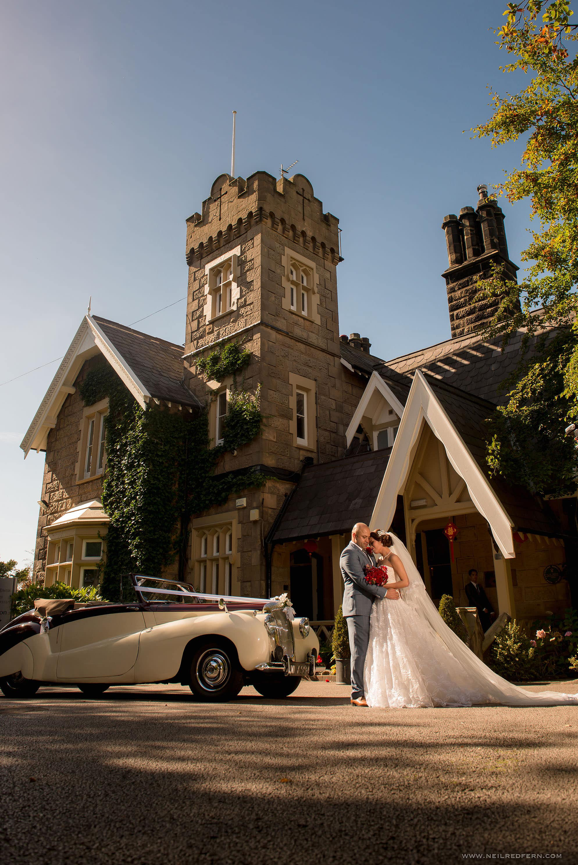 bride and groom with car outside West Tower