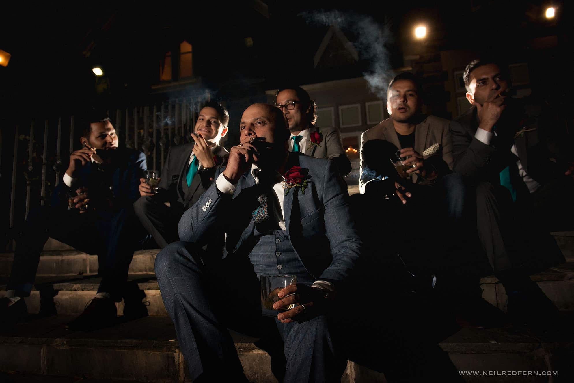 cool shot of groomsmen smoking cigars