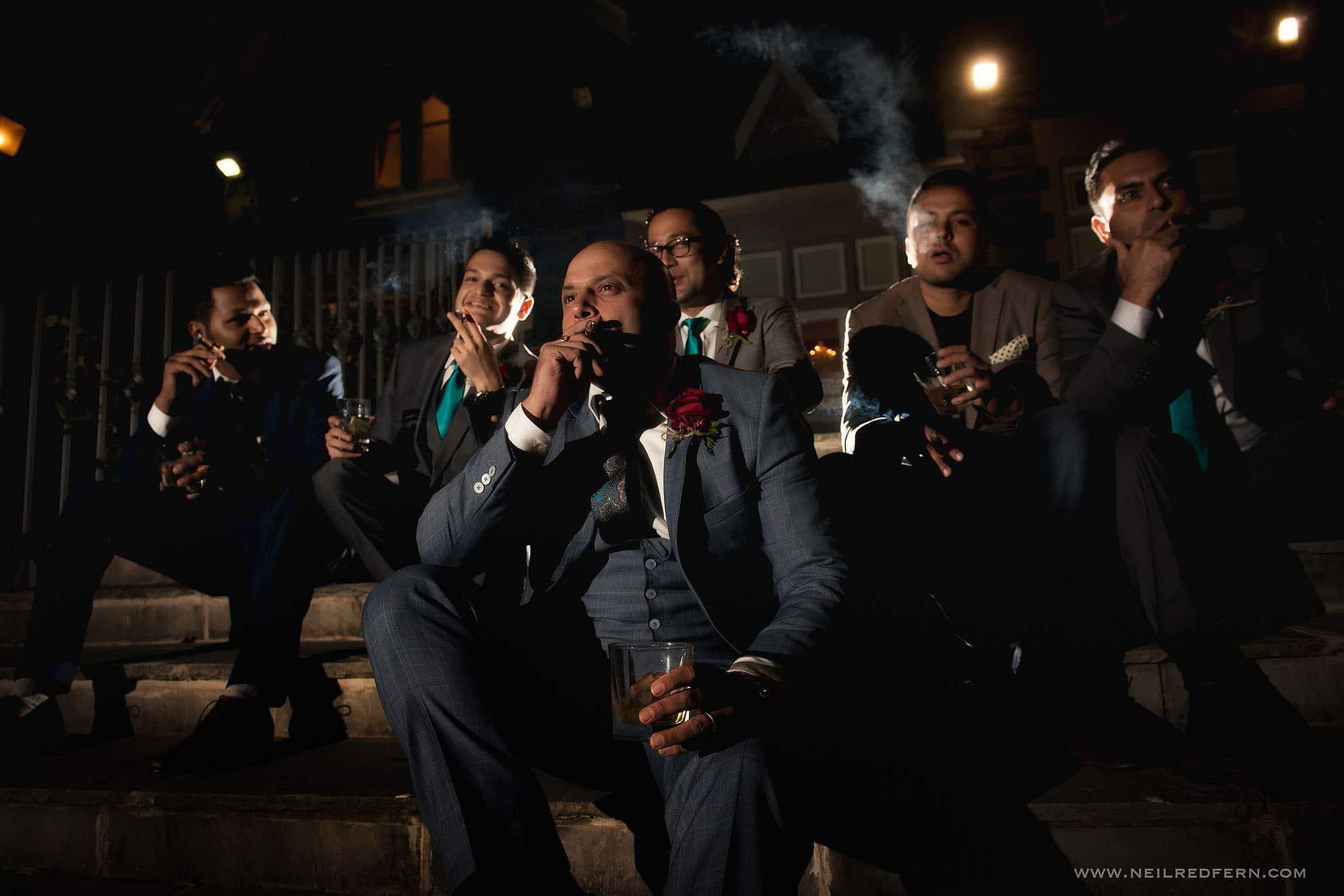 cool shot of groomsmen smoking cigars