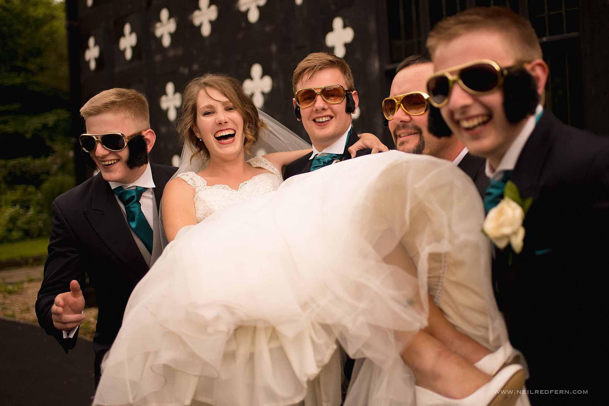 groomsmen picking up bride