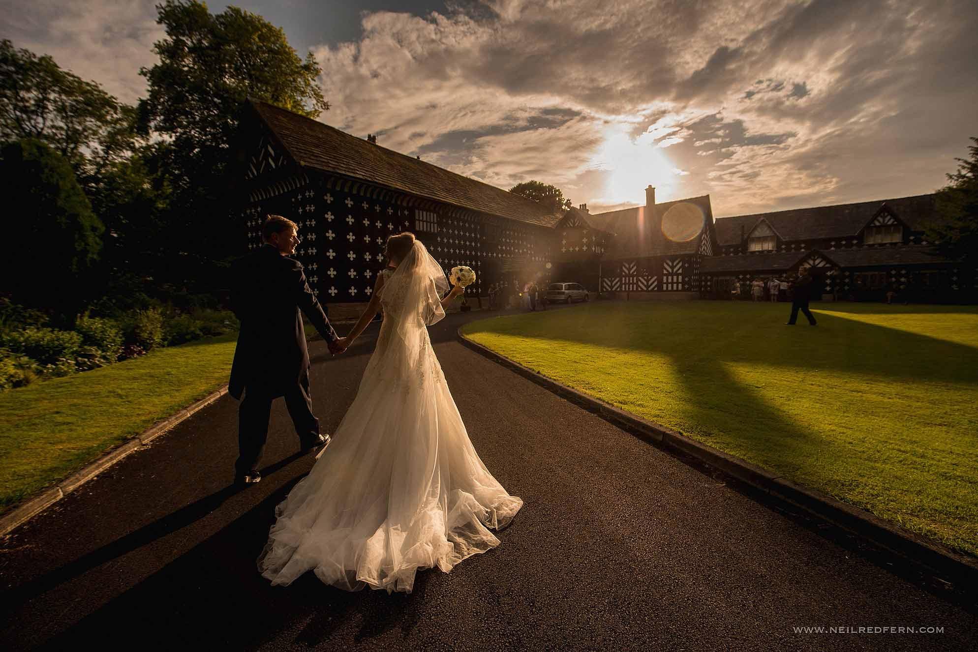 bride and groom walking towards Samlesbury Hall