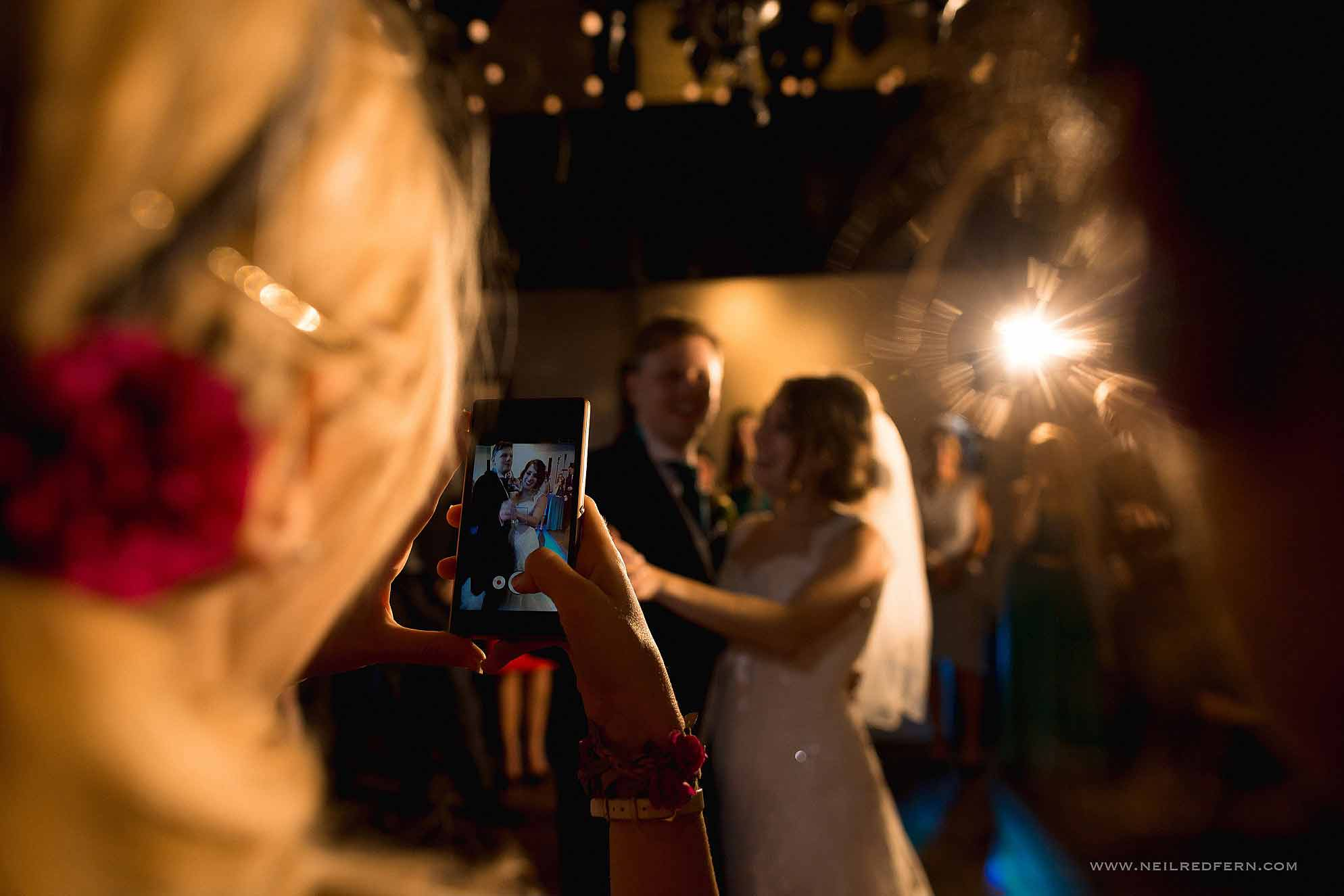 guest filming first dance on phone