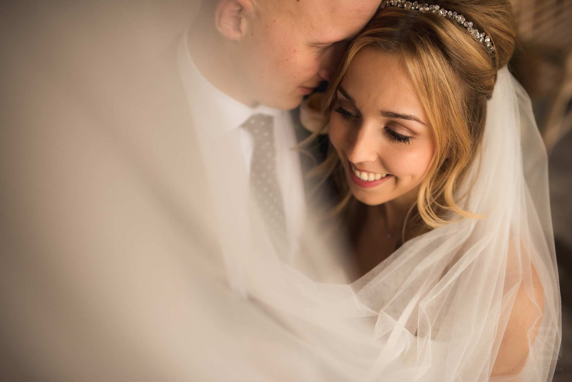 bride and groom photographed through veil