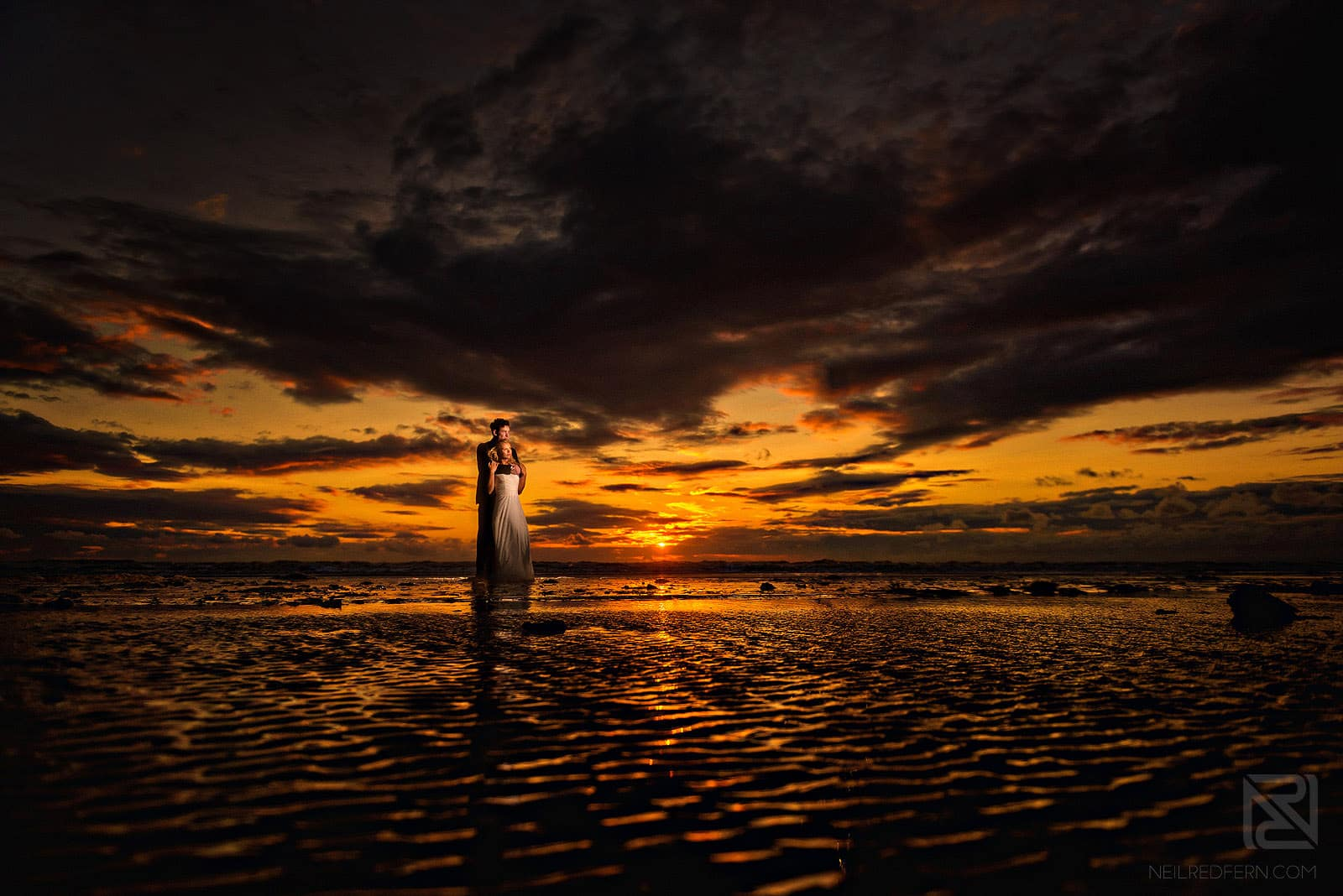 romantic photo of bride and groom on a beach at sunset