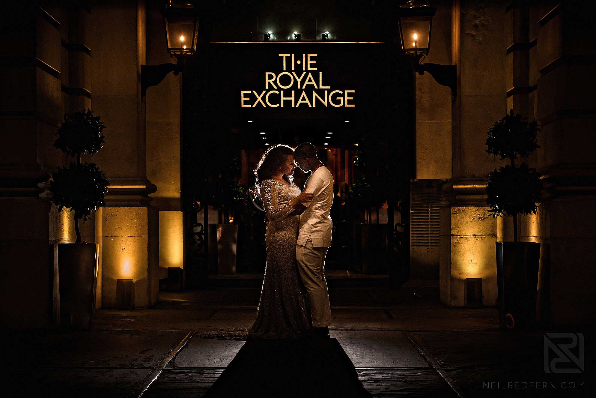 night time photograph of bride and groom outside The Royal Exchange London