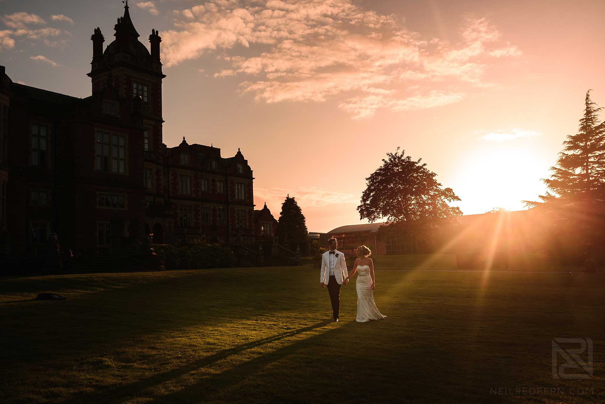 bride and groom walking in gardens of Crewe Hall at sunset