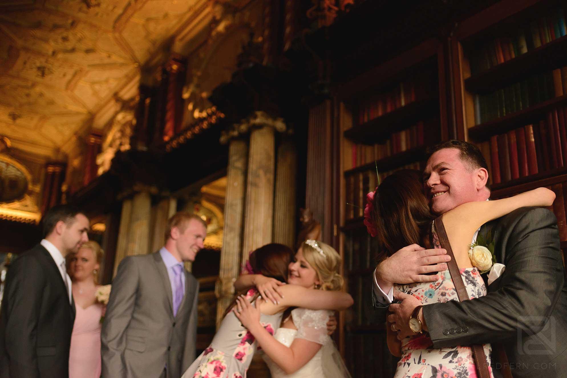 bride and groom hugging guests