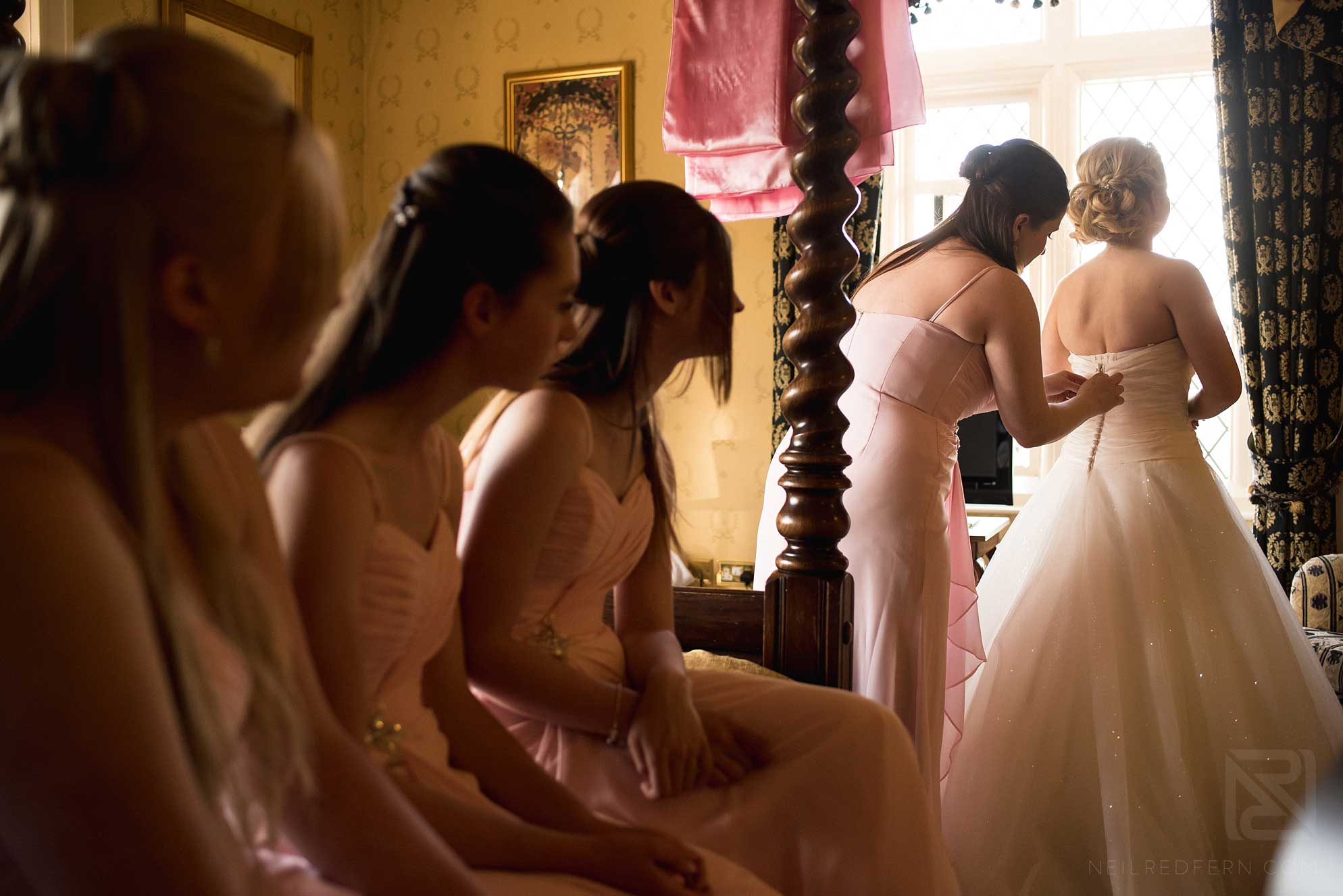 bridesmaids helping bride get in to dress