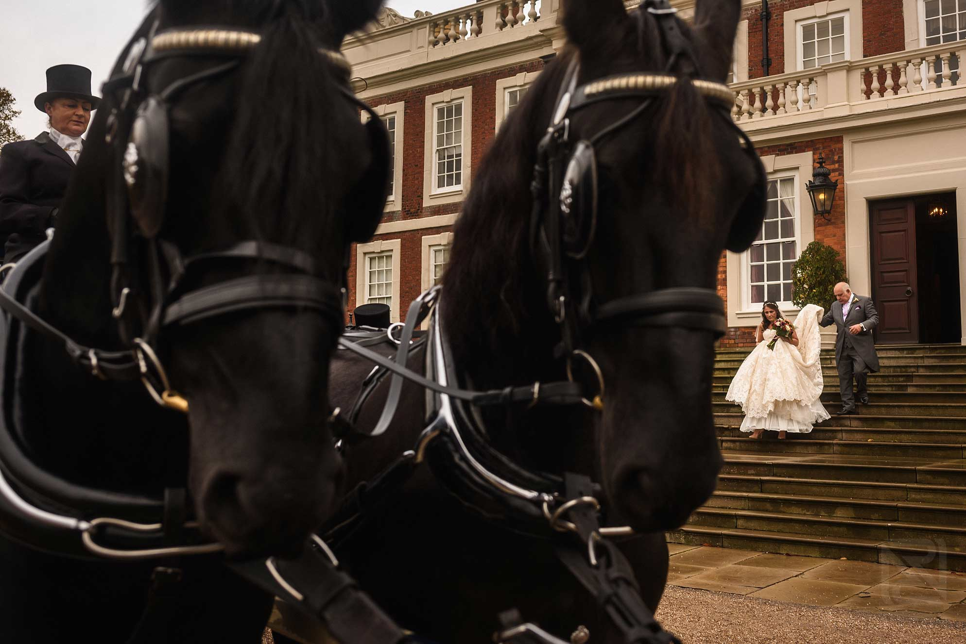 bride and gather going to church in horse drawn carriage