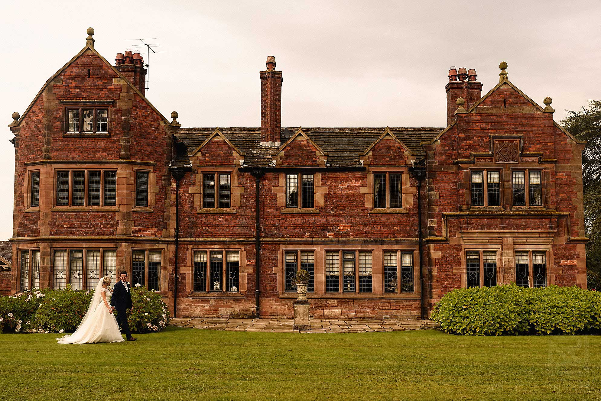 bride and groom walking past Colshaw Hall