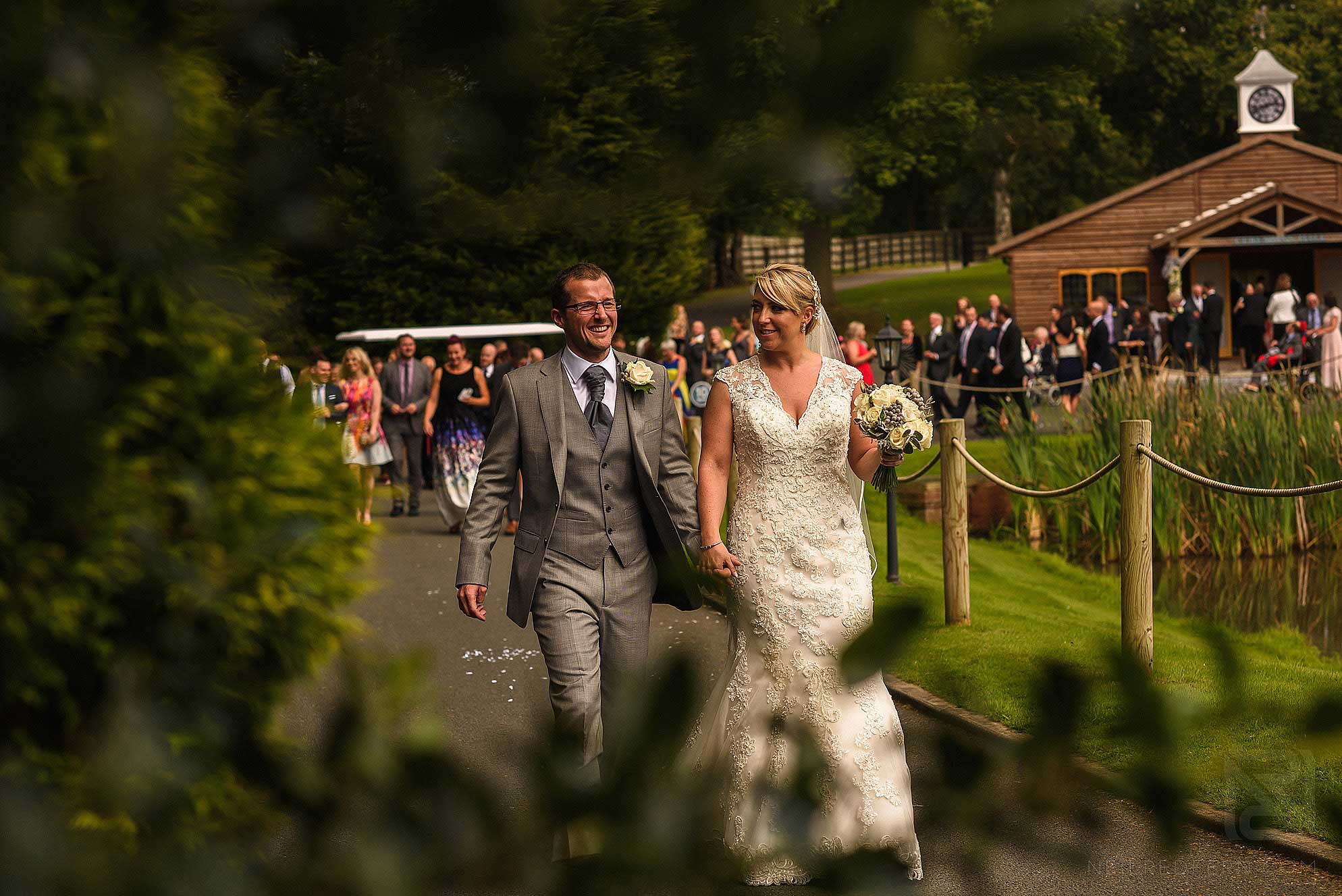 bride and groom walking through gardens at Colshaw Hall