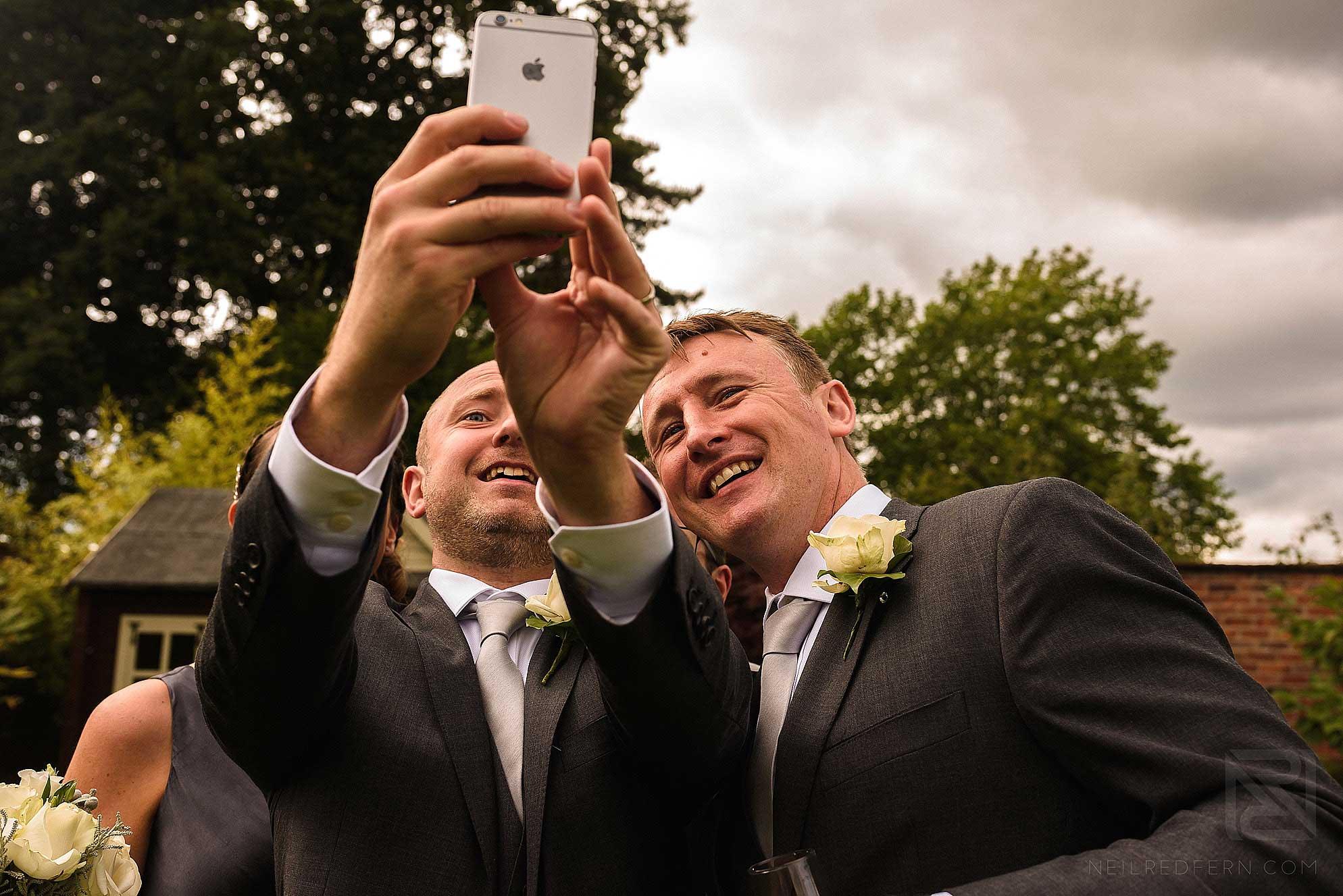 groomsmen taking photographs with phone