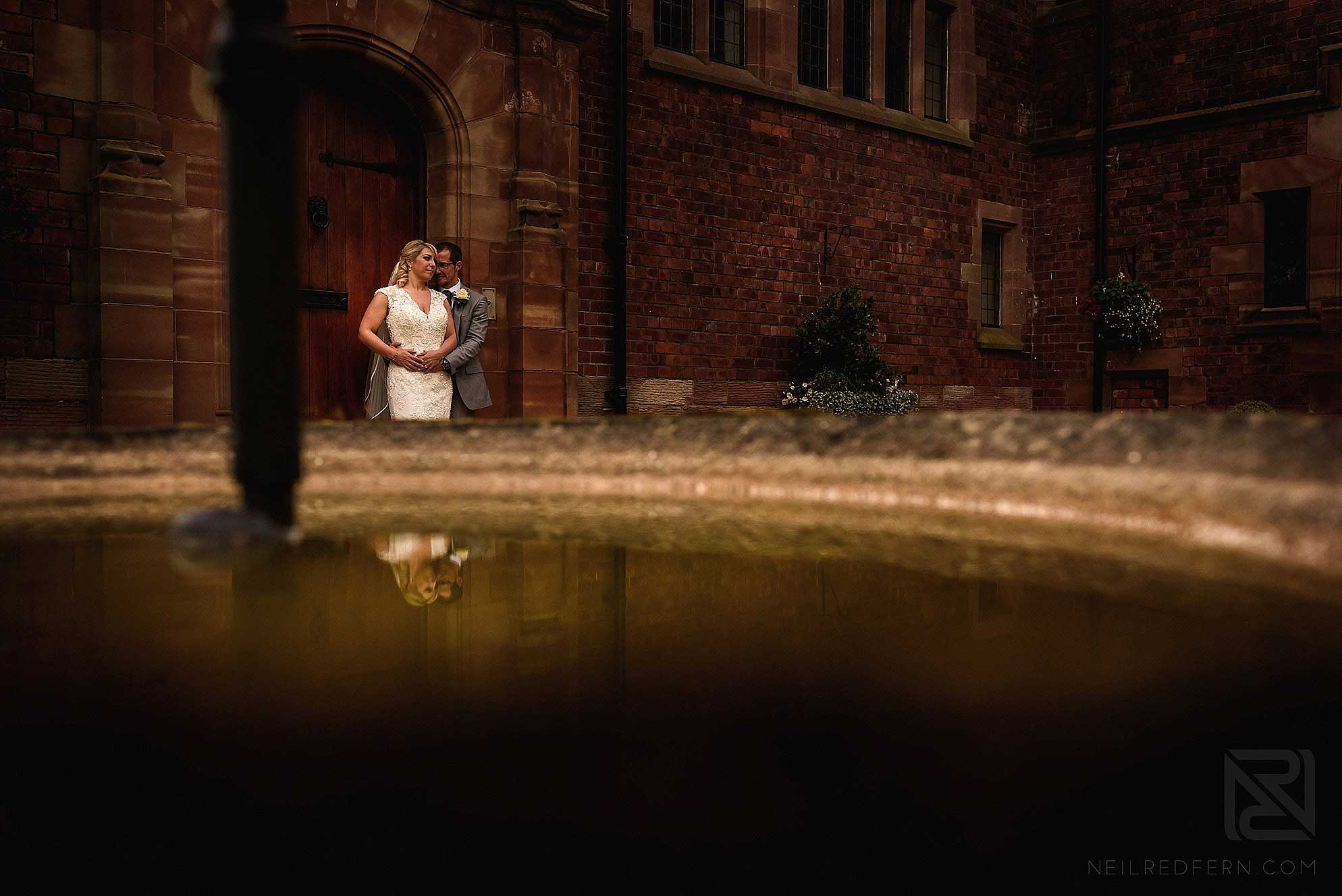 reflection of bride and groom in fountain