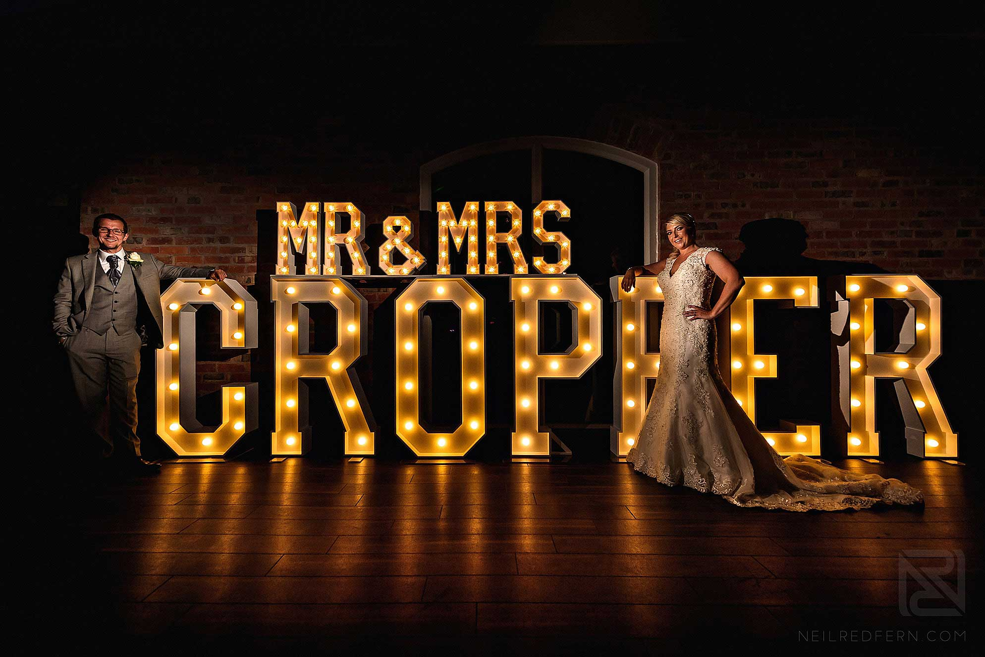 couple stood in front of large letters at wedding
