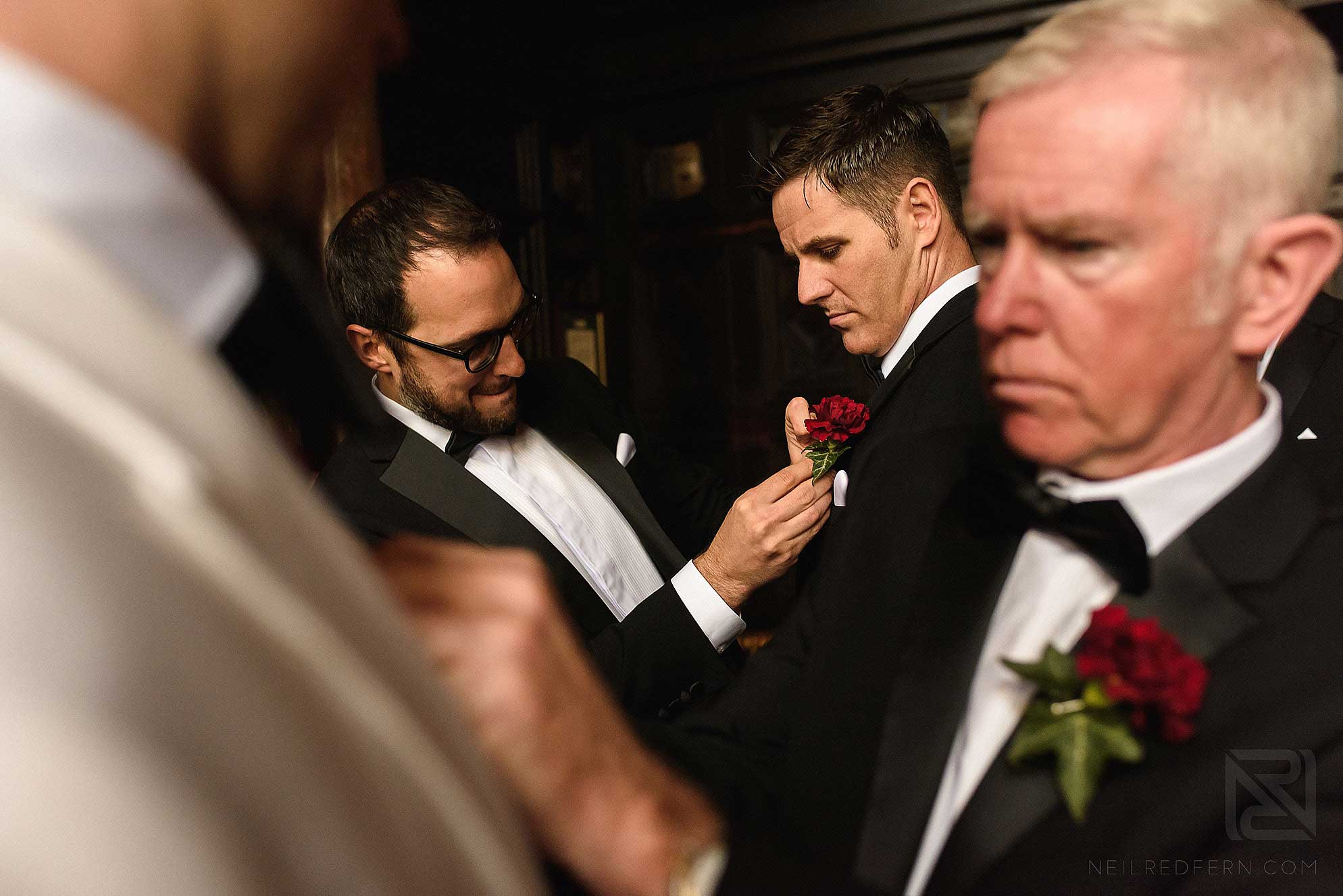groomsmen putting on button holes