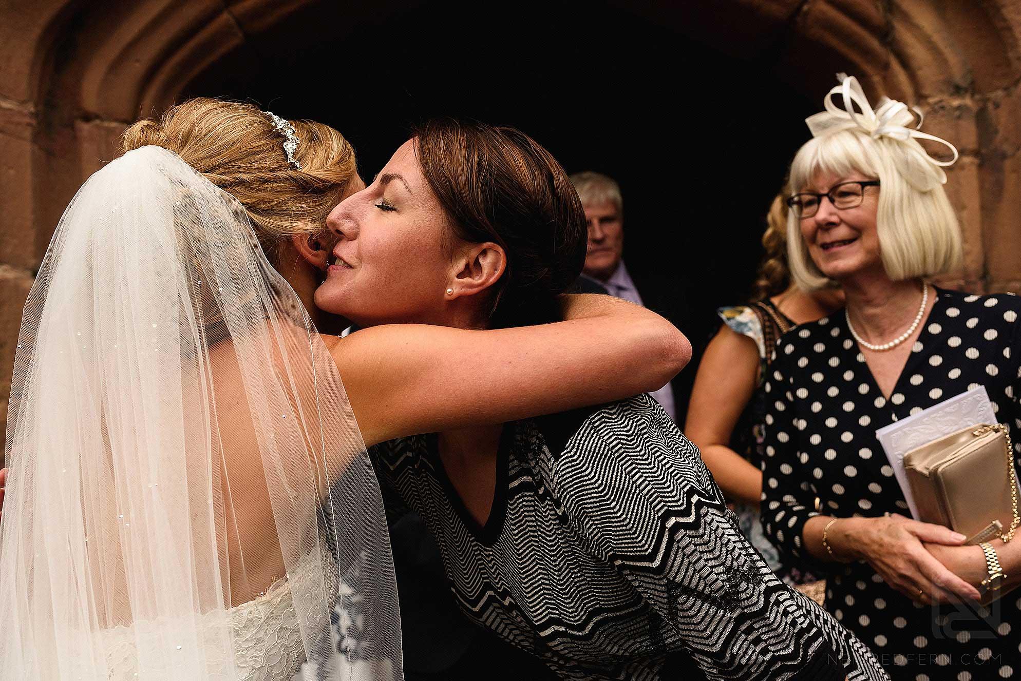 bride hugging friend outside church