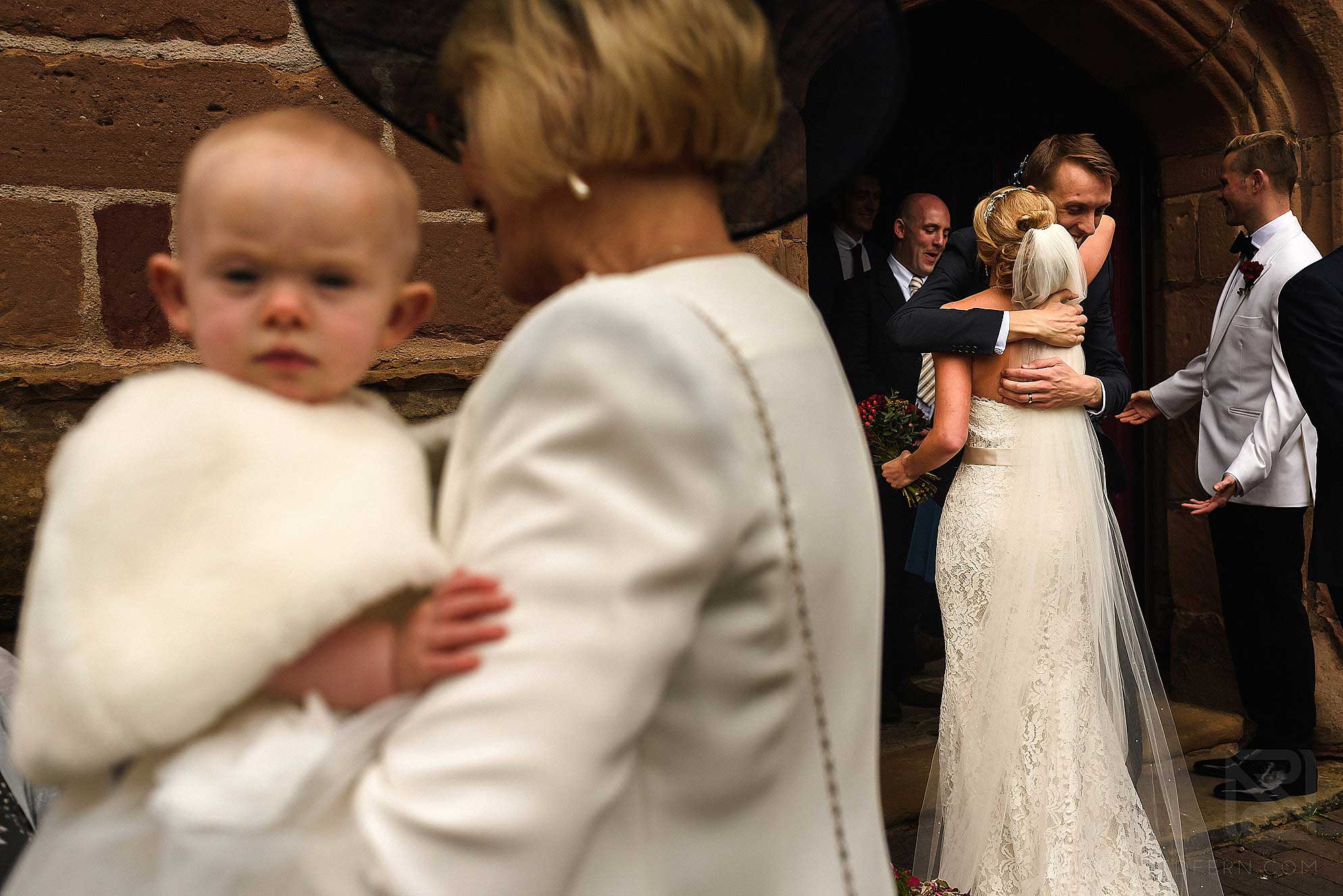 bride hugging guests as they leave church