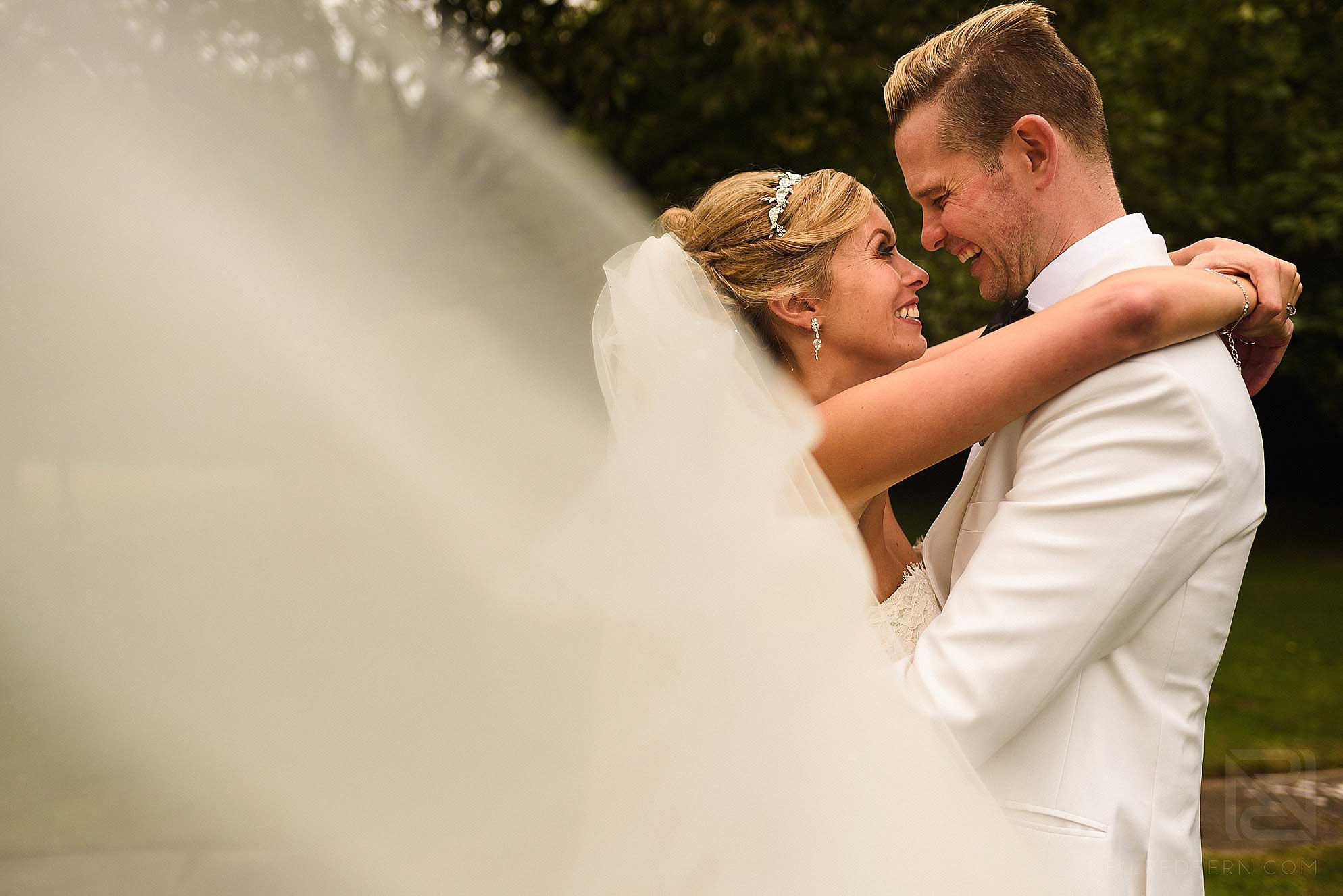 bride and groom smiling with veil