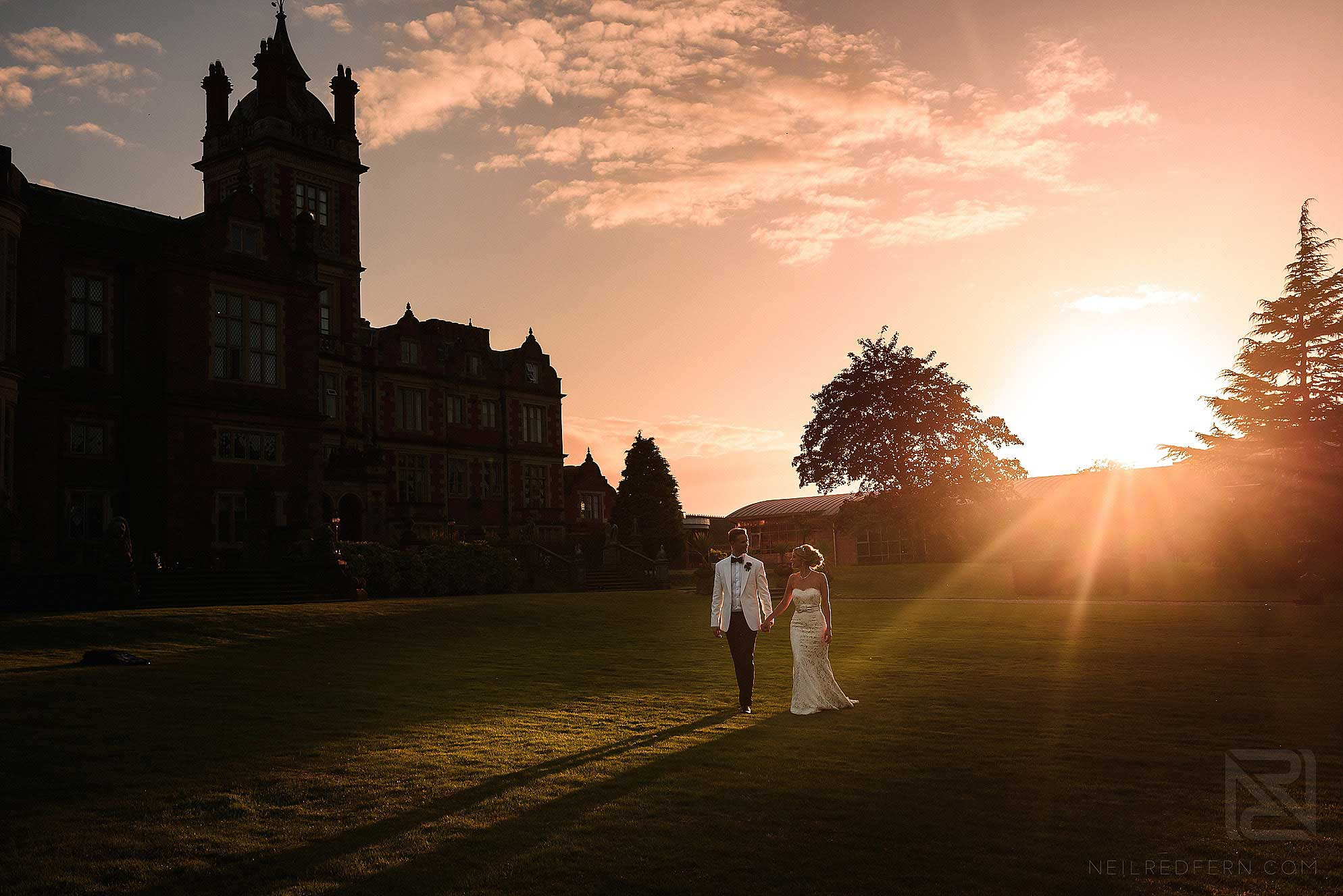 bride and groom walking through the gardens at Crewe Hall in Cheshire