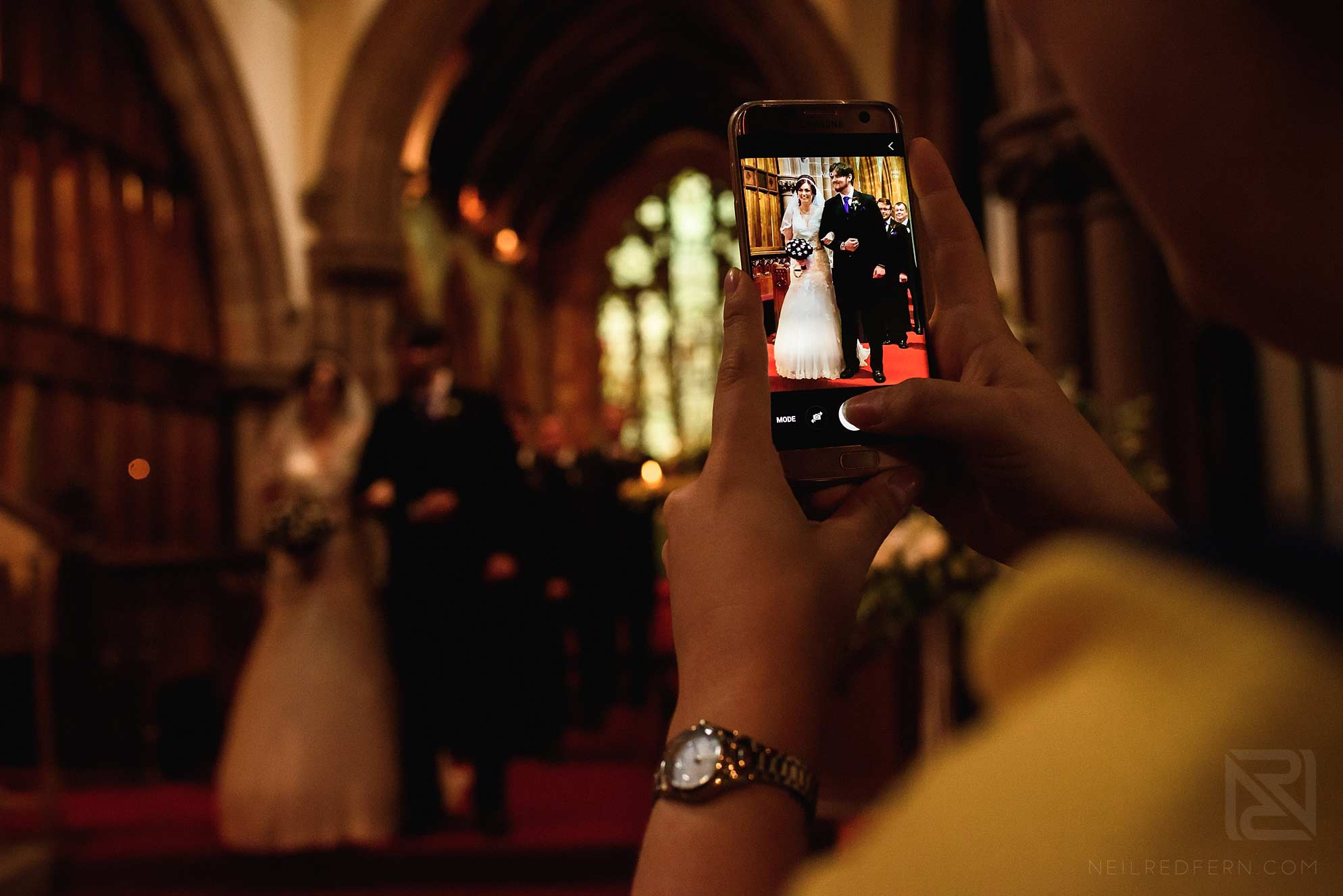 wedding guest taking photograph on phone