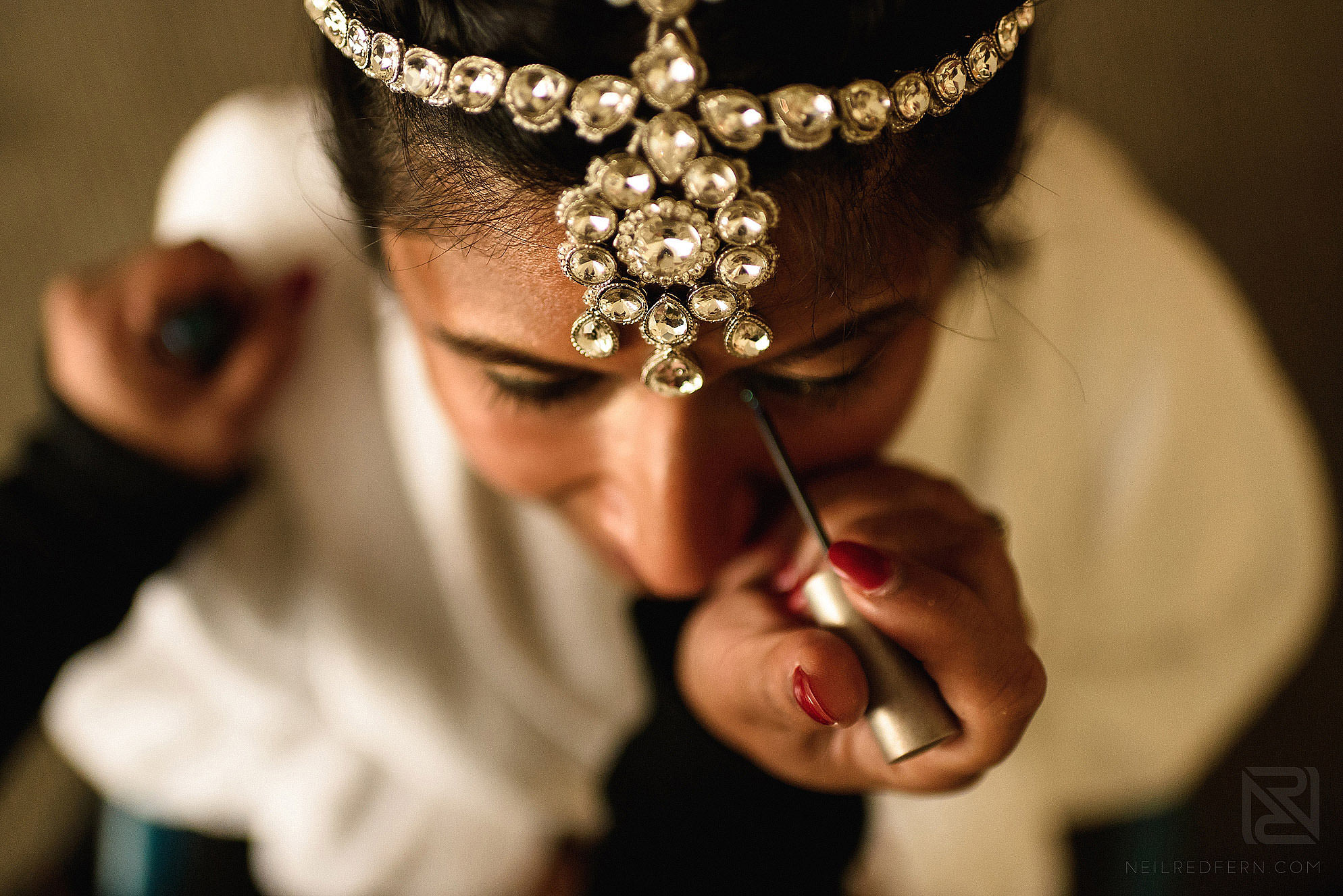 Hindu bride putting on make-up