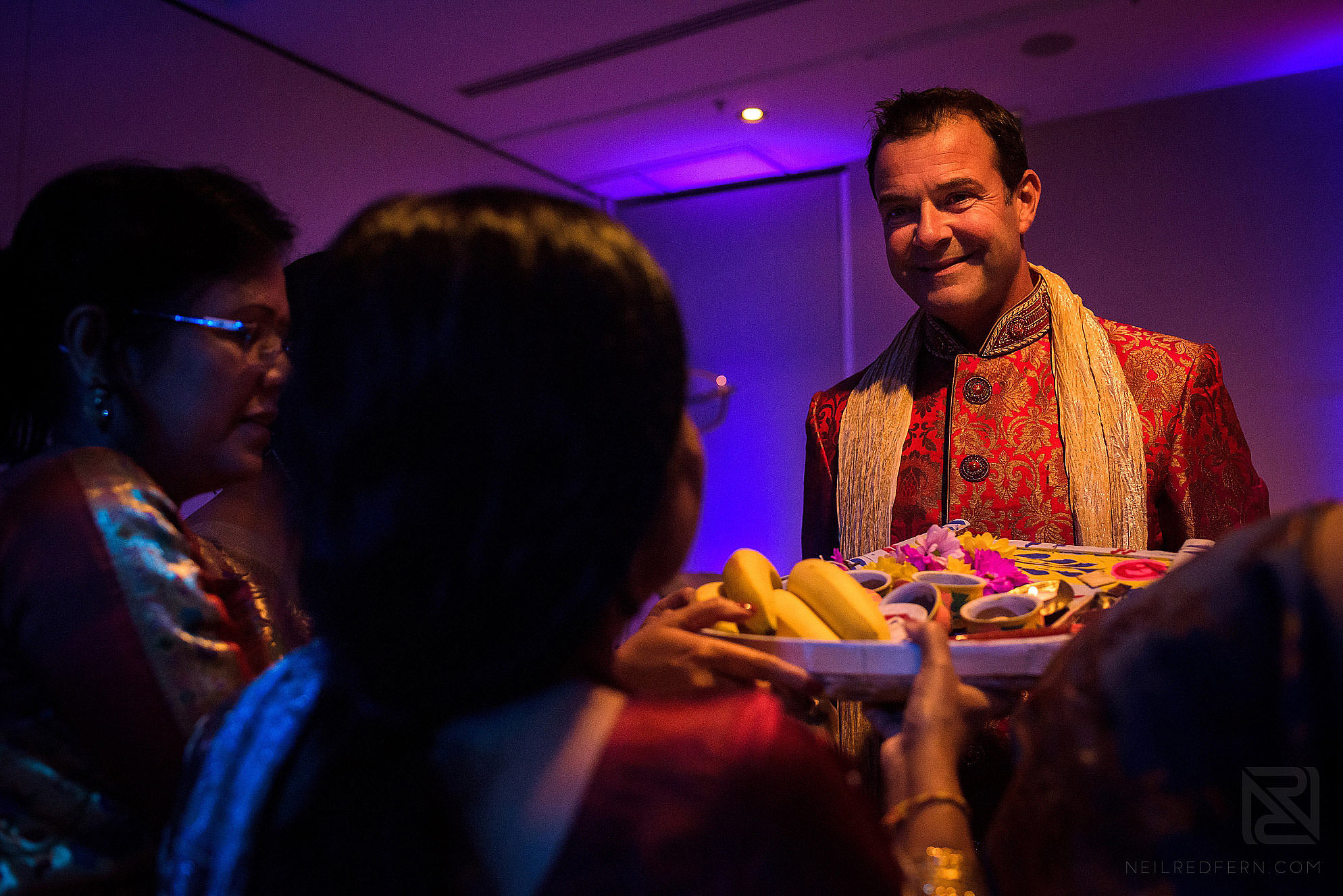 groom being offered food during wedding ceremony