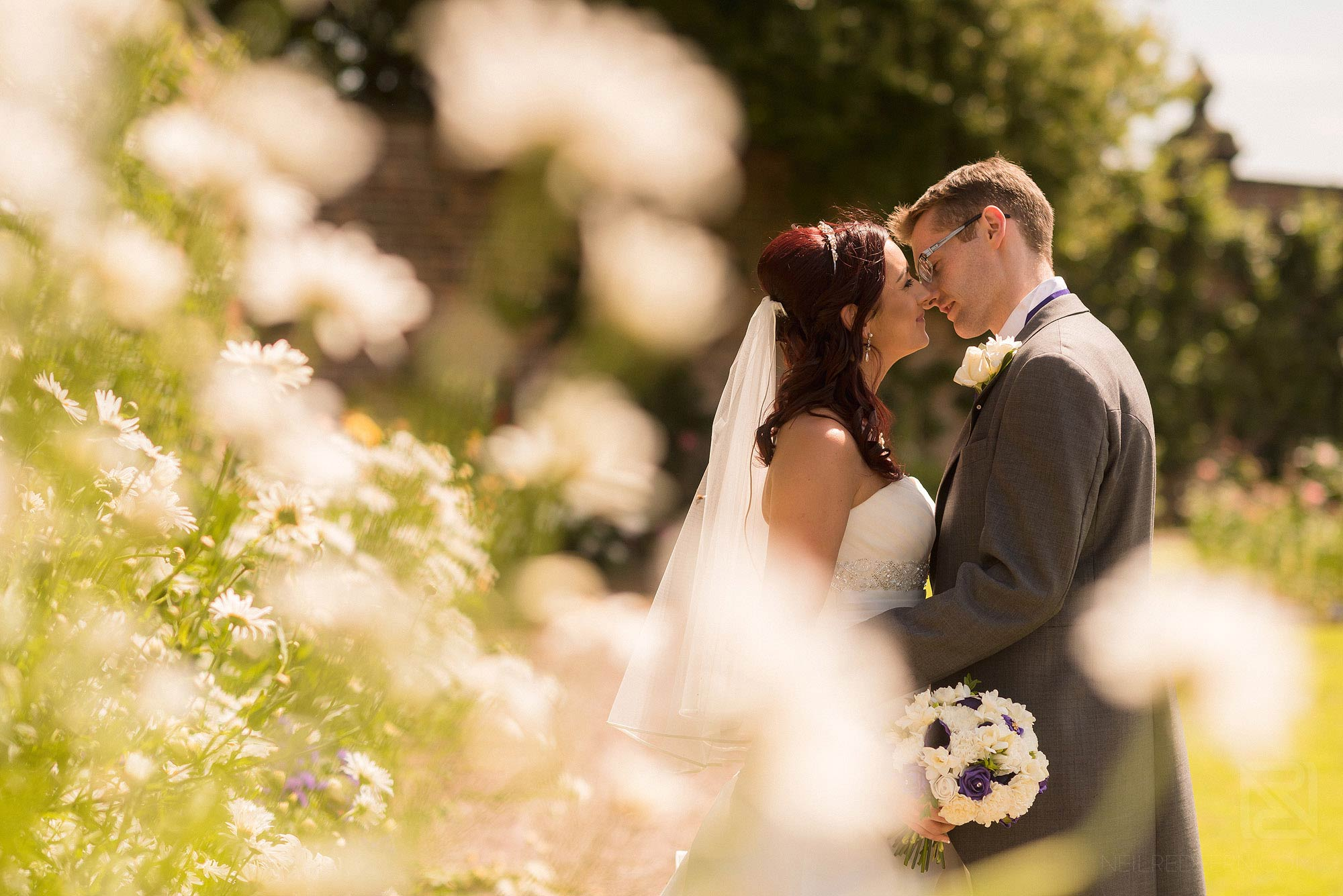 newlyweds kissing in Arley Hall gardens