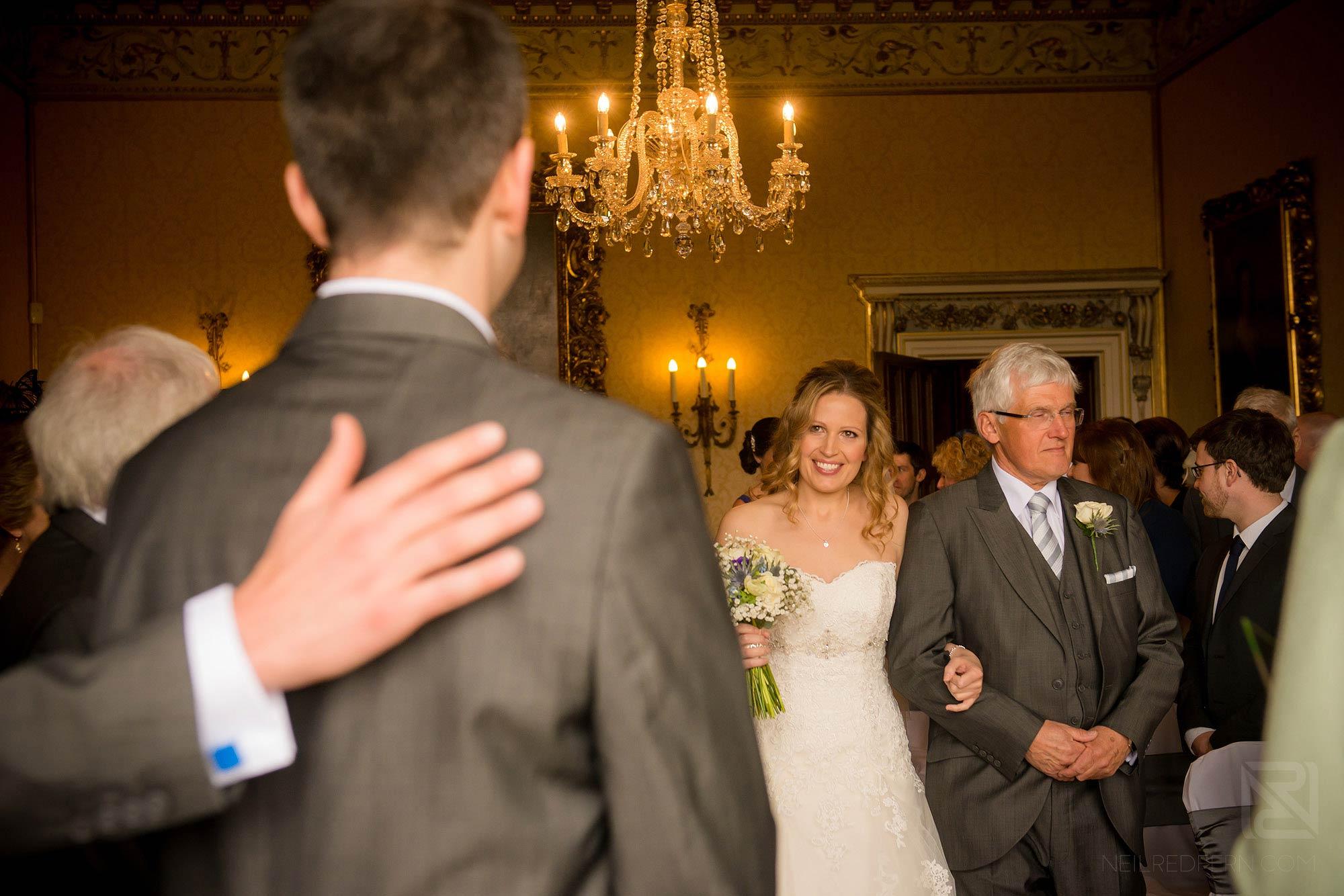 bride walking down aisle looking at groom
