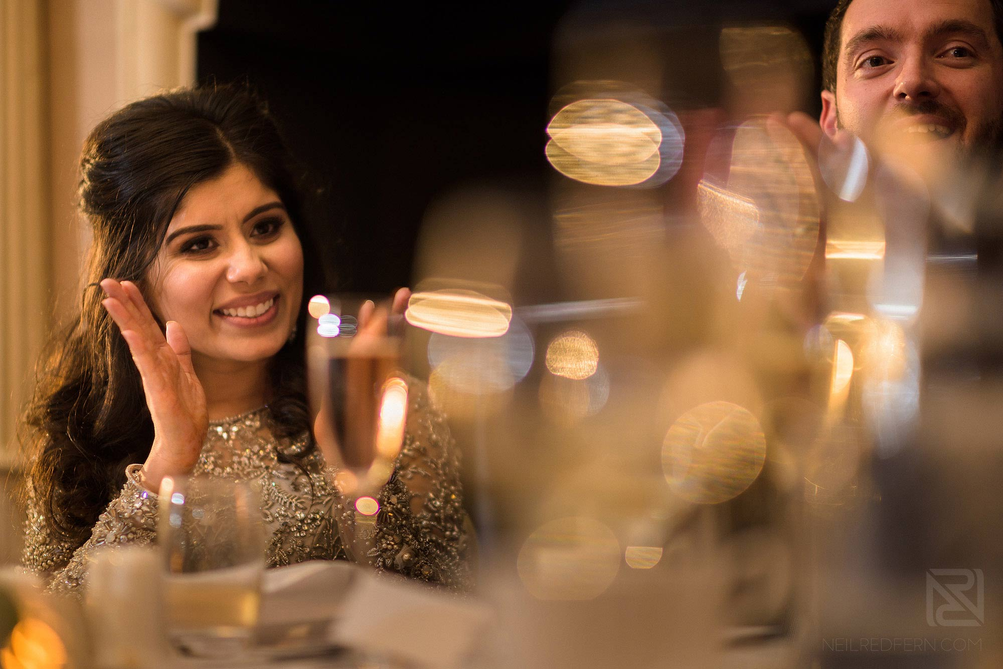 bride smiling during wedding speeches