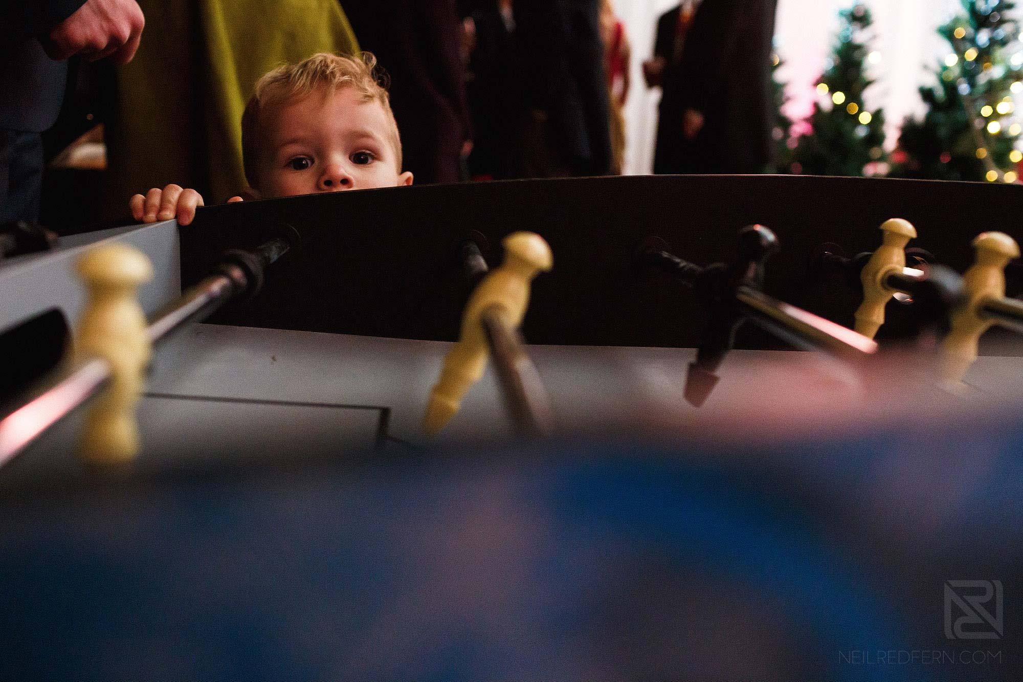 little boy play air hockey at wedding