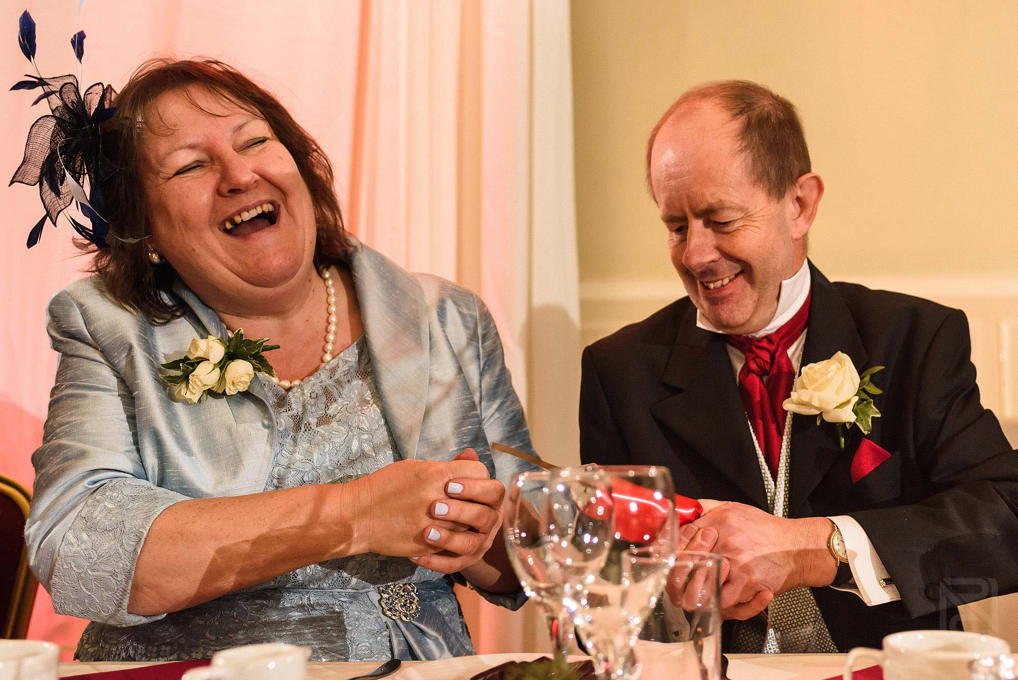 parents pulling a Christmas cracker at wedding