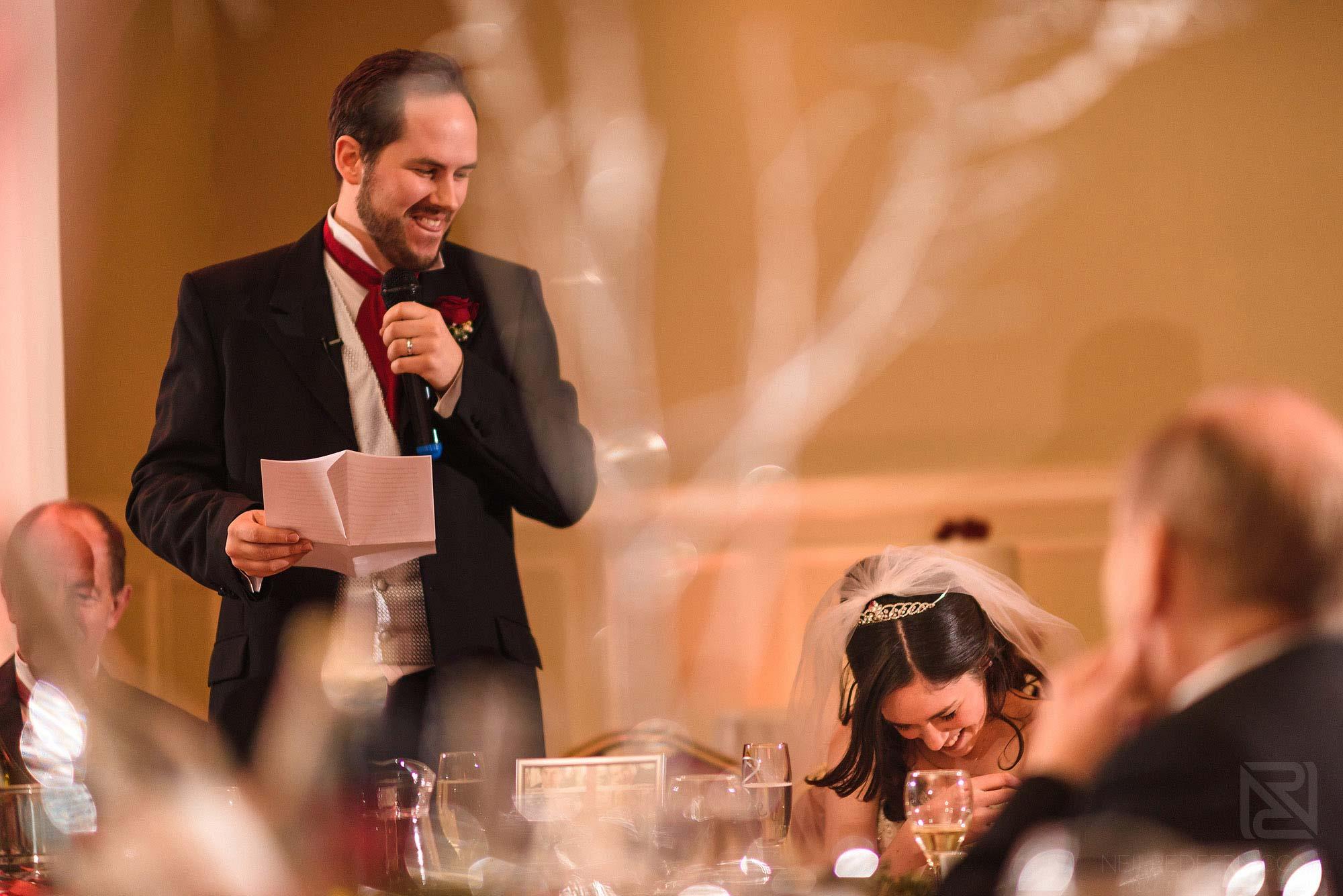 bride laughing during groom's wedding speech