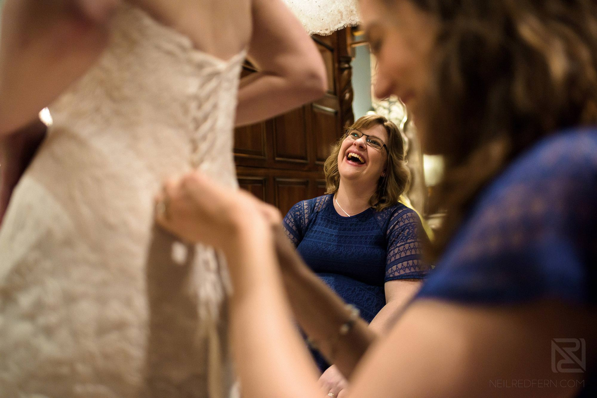 bridesmaids laughing putting bride in to wedding dress