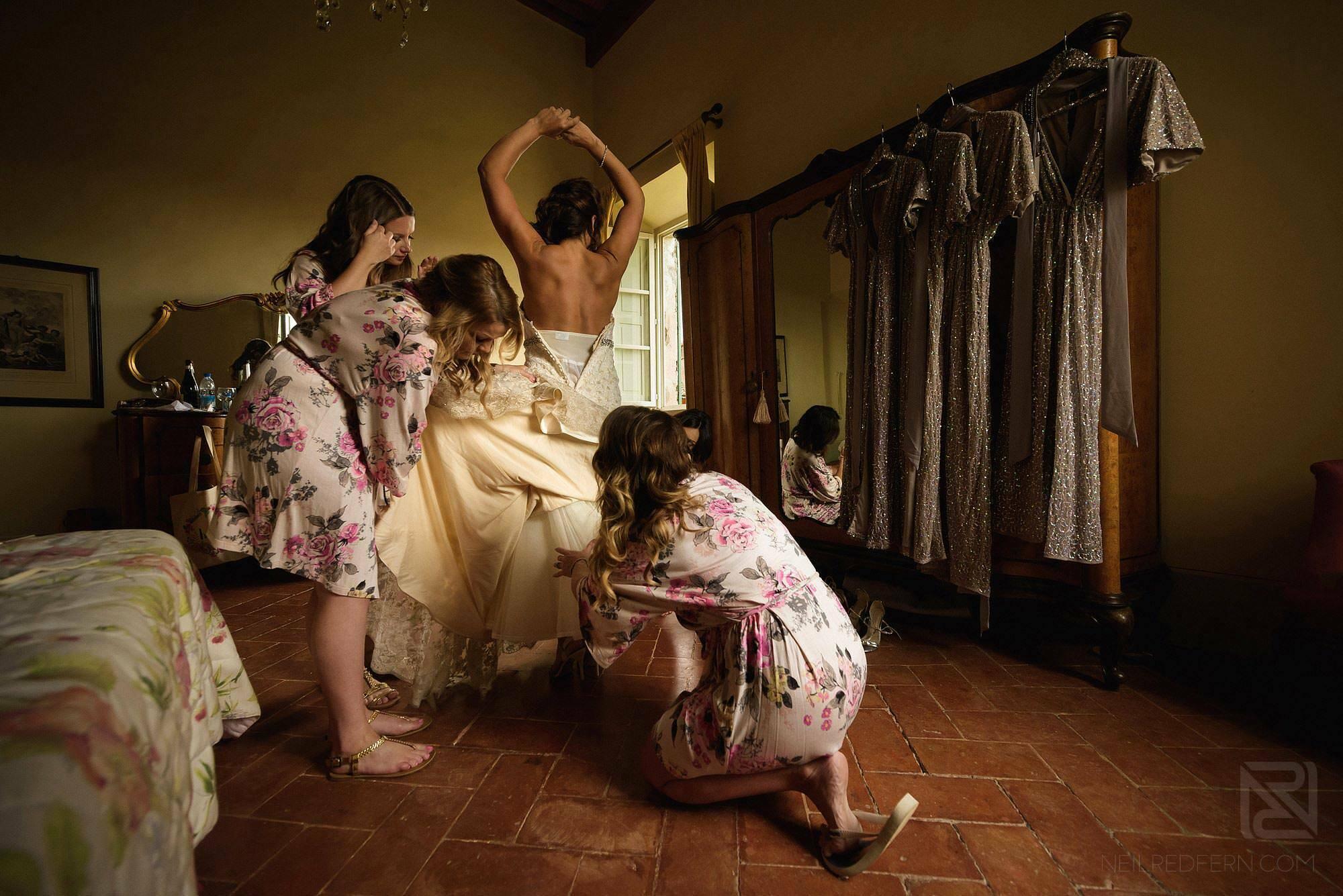 bride putting on wedding dress in Tuscany