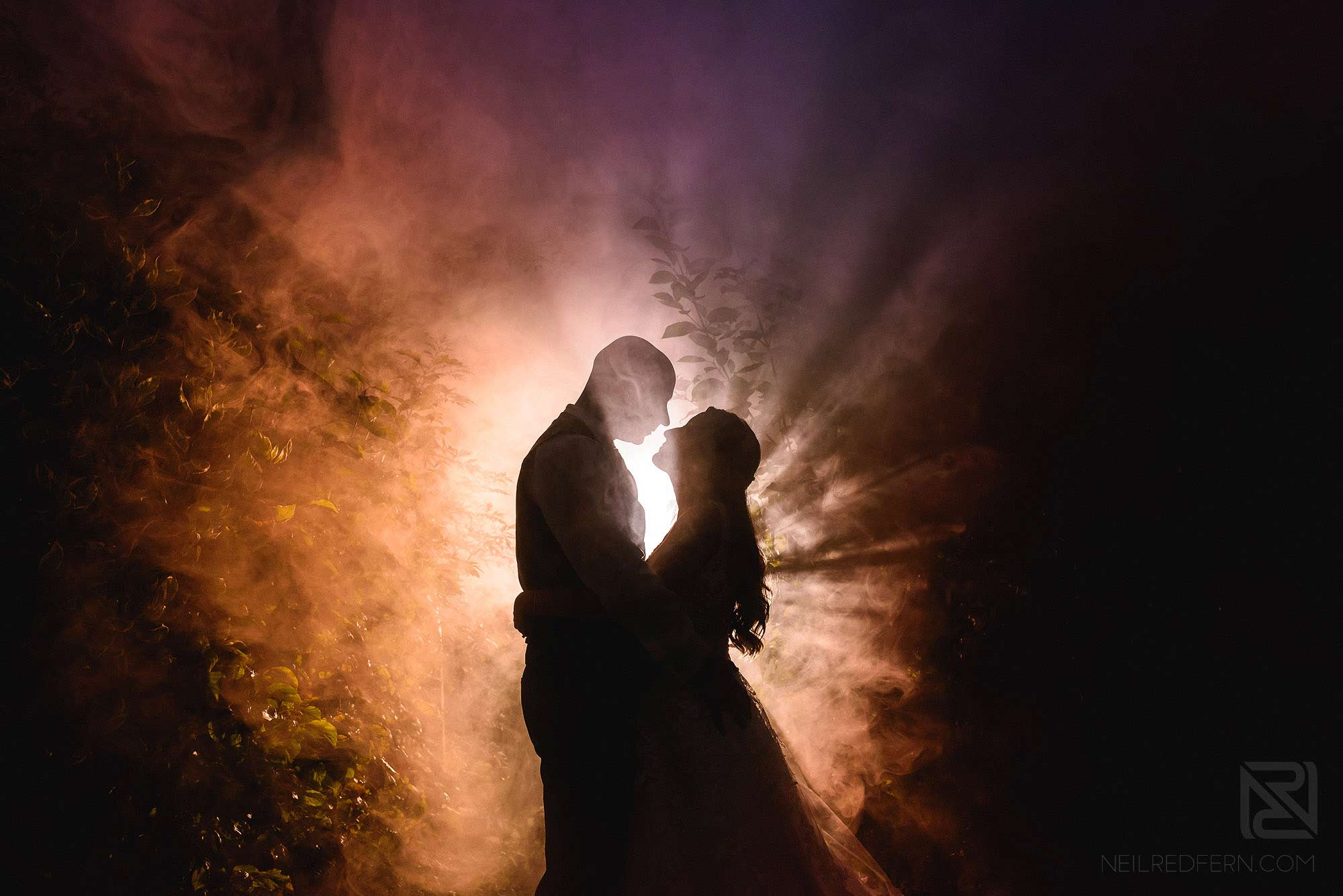 creative portrait of bride and groom with smoke