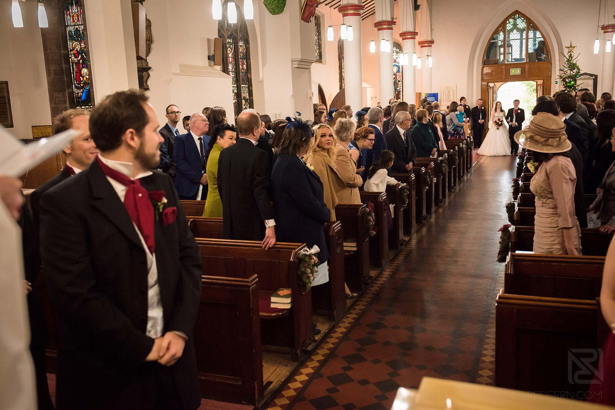 bride walking down aisle in St James' Church in Didsbury