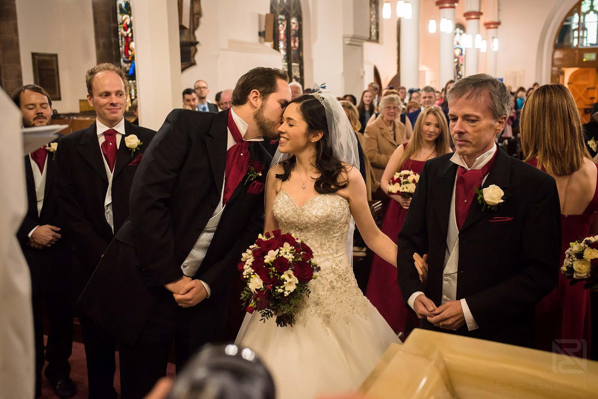 groom kissing bride during wedding ceremony