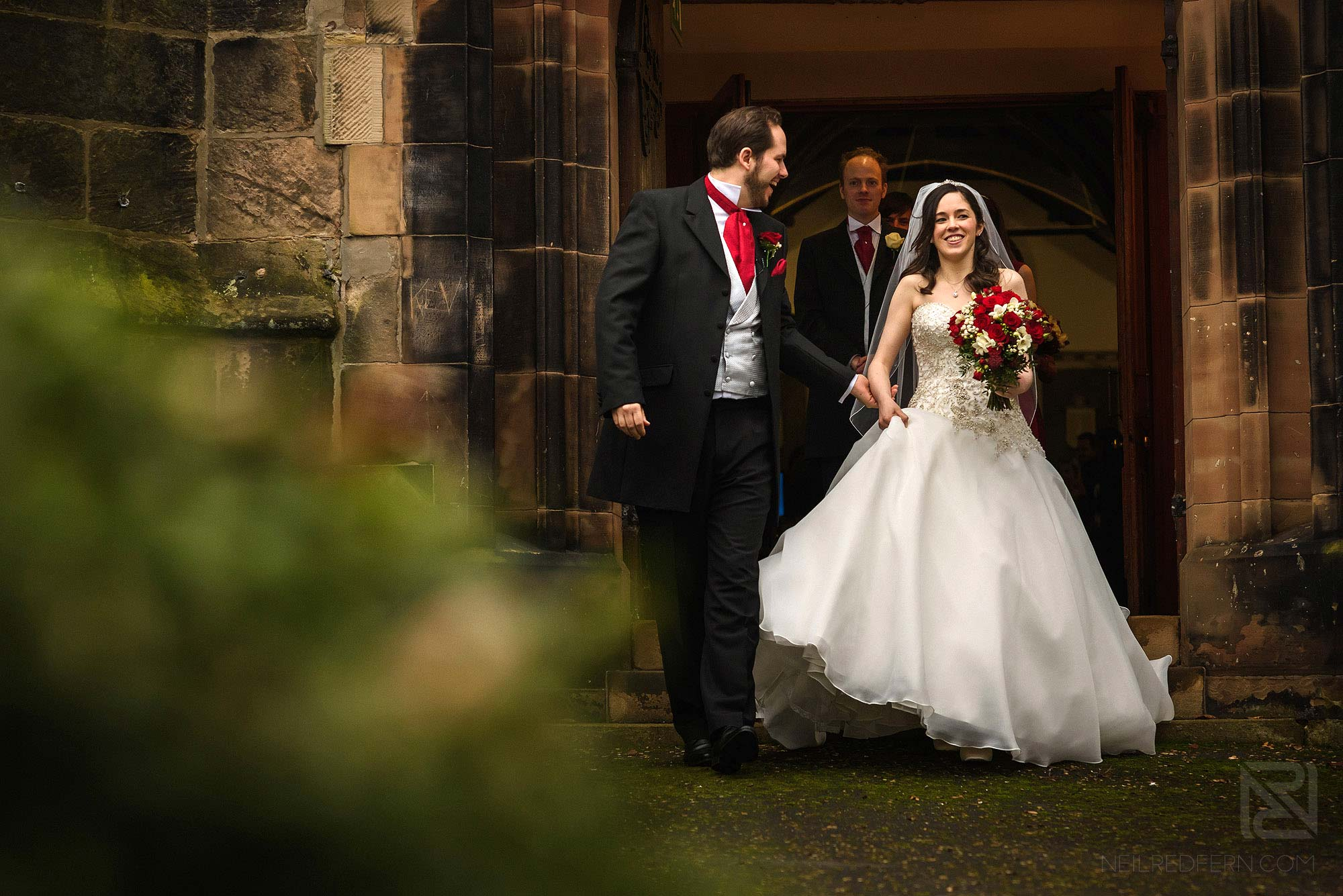 bride and groom leaving church together