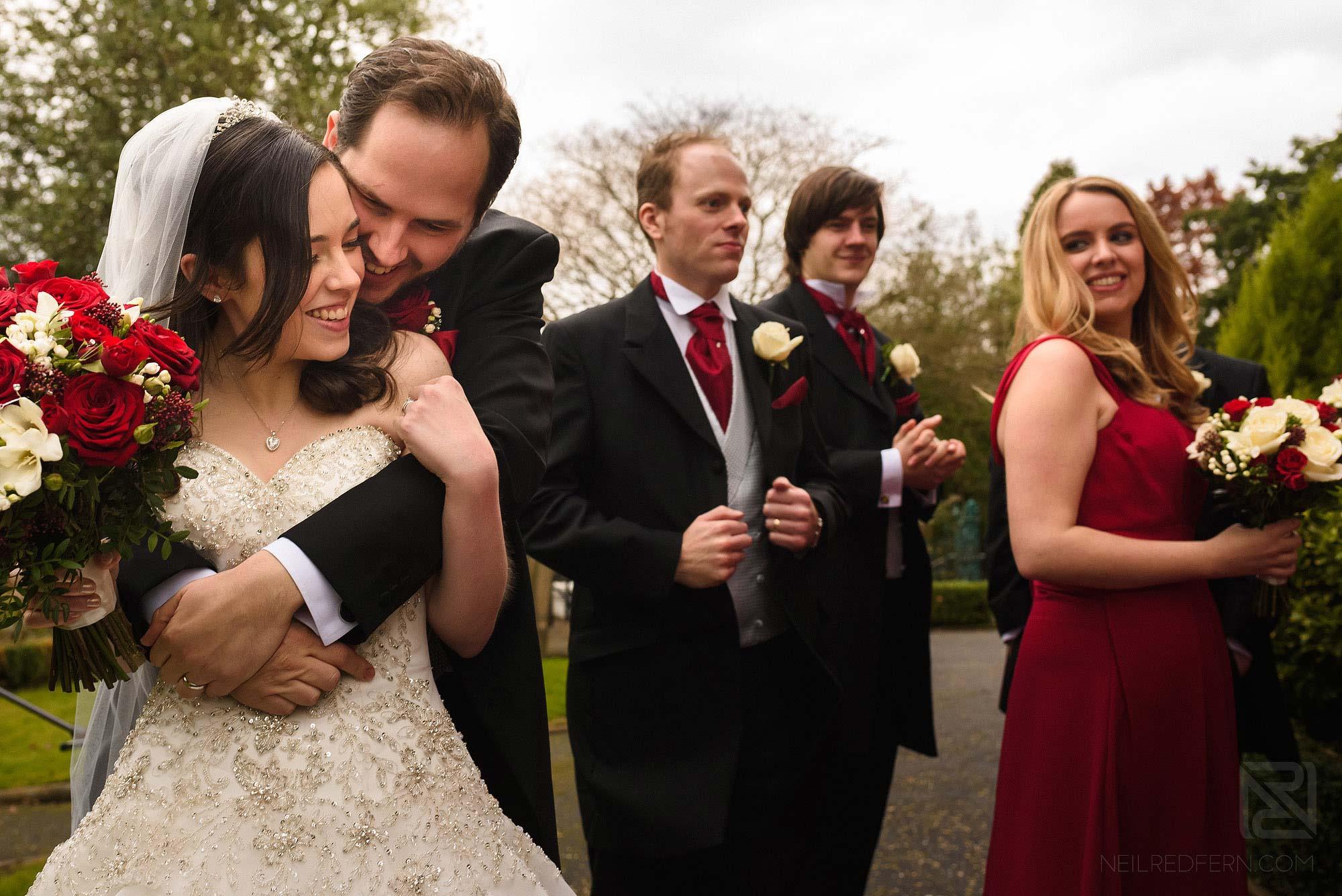 groom hugging bride outside church