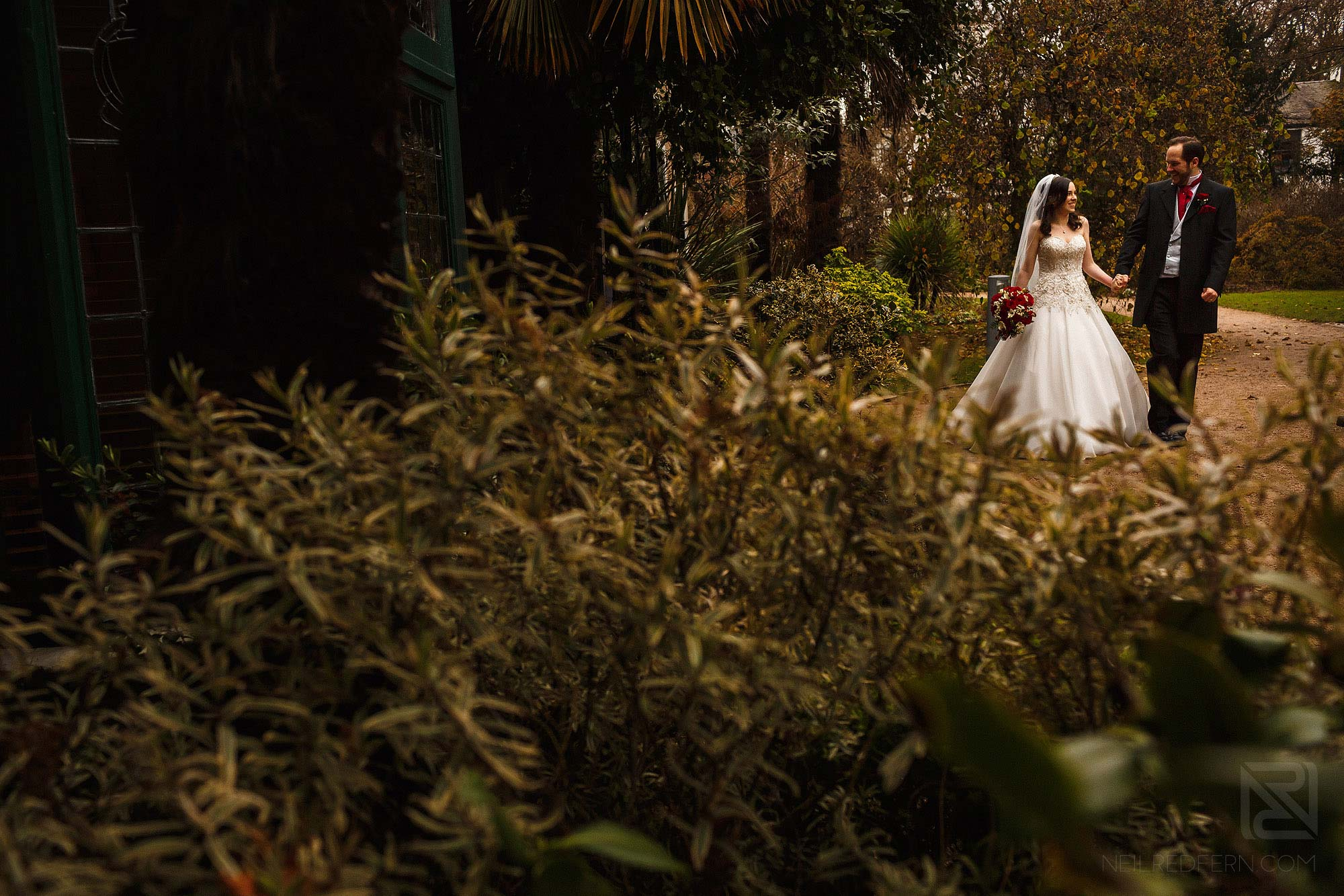 bride and groom walking through park in Manchester