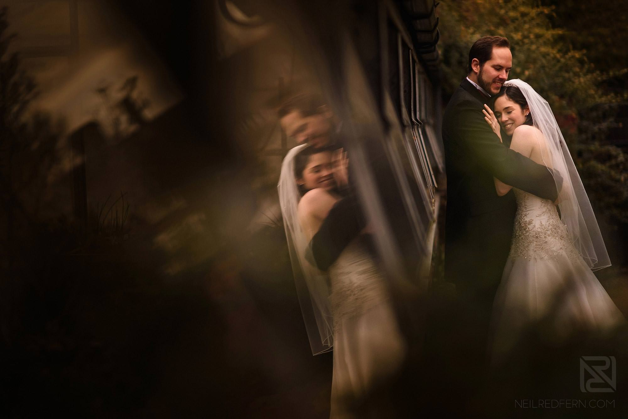 romantic photograph of bride and groom with reflection in glass