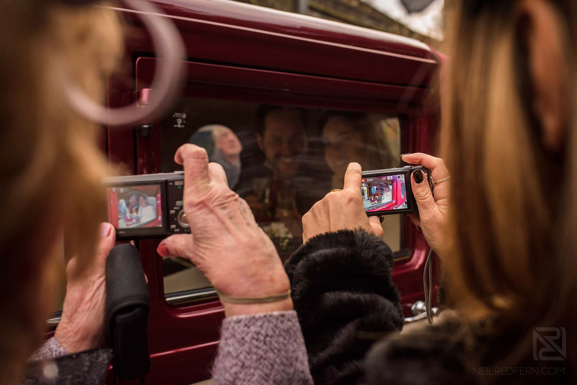 guests taking photograph of newlyweds in car