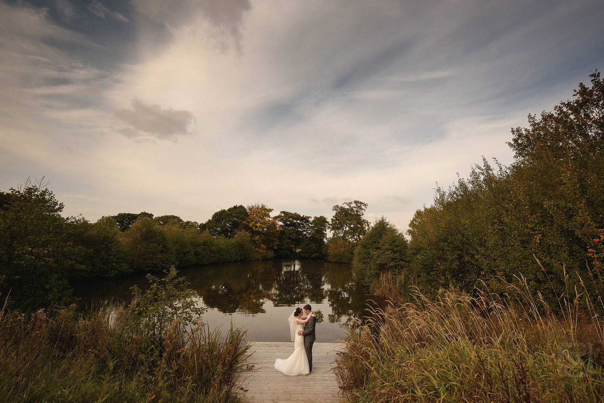 bride and groom standing by lake at Styal Lodge