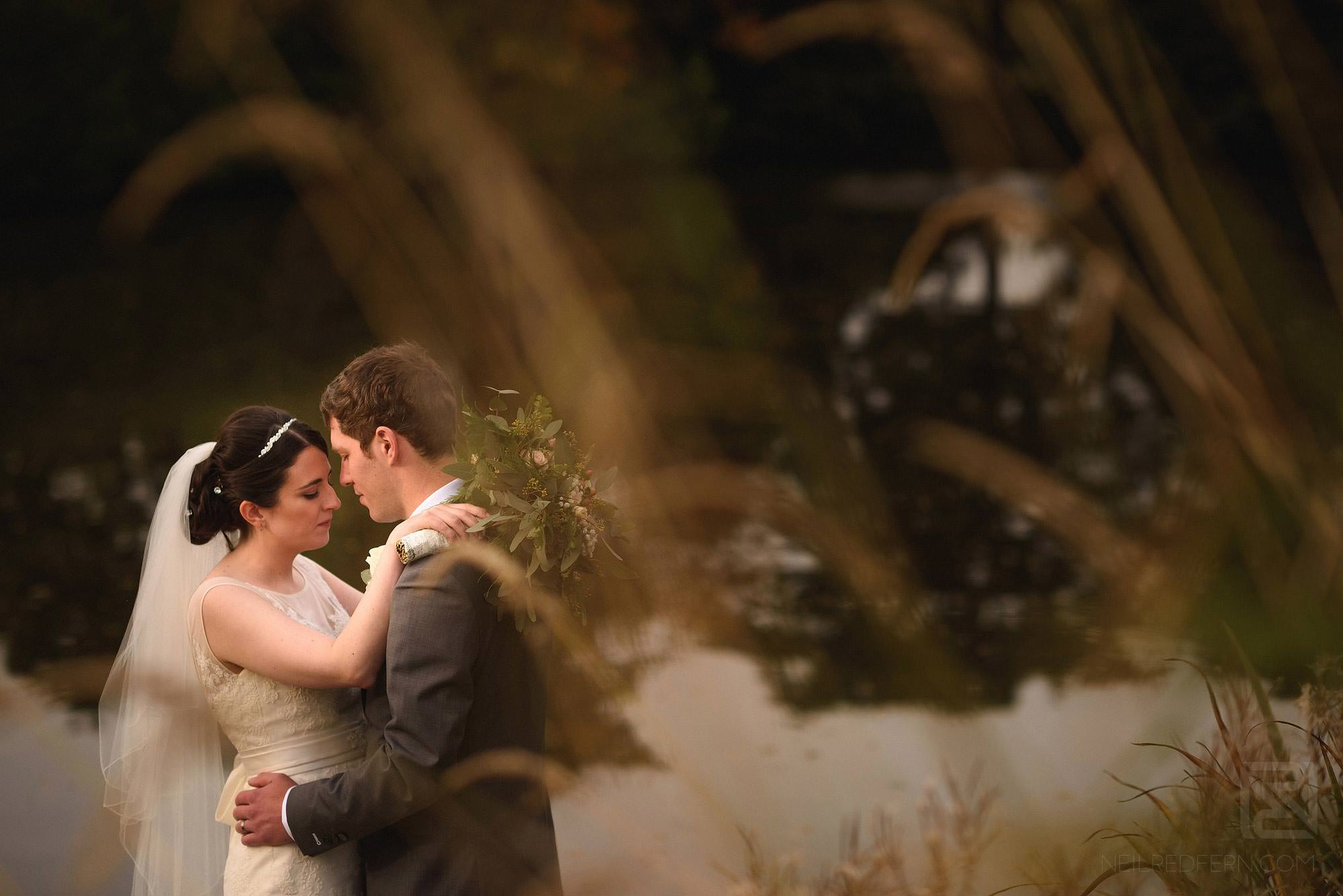 romantic photograph of bride and groom by a lake