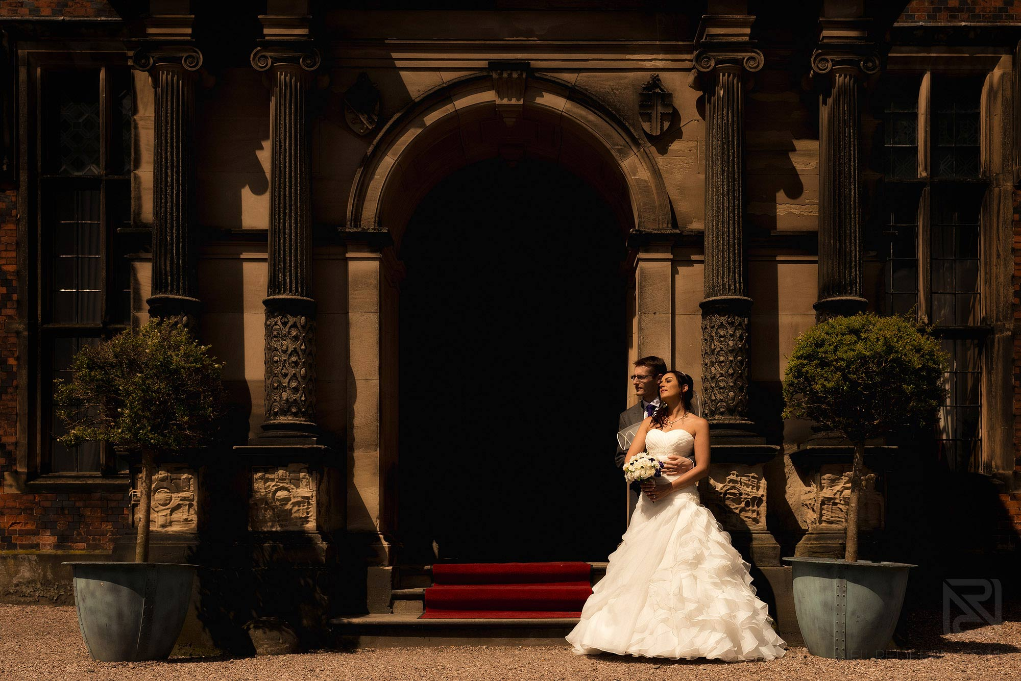 bride and groom stood outside Arley Hall in sunshine