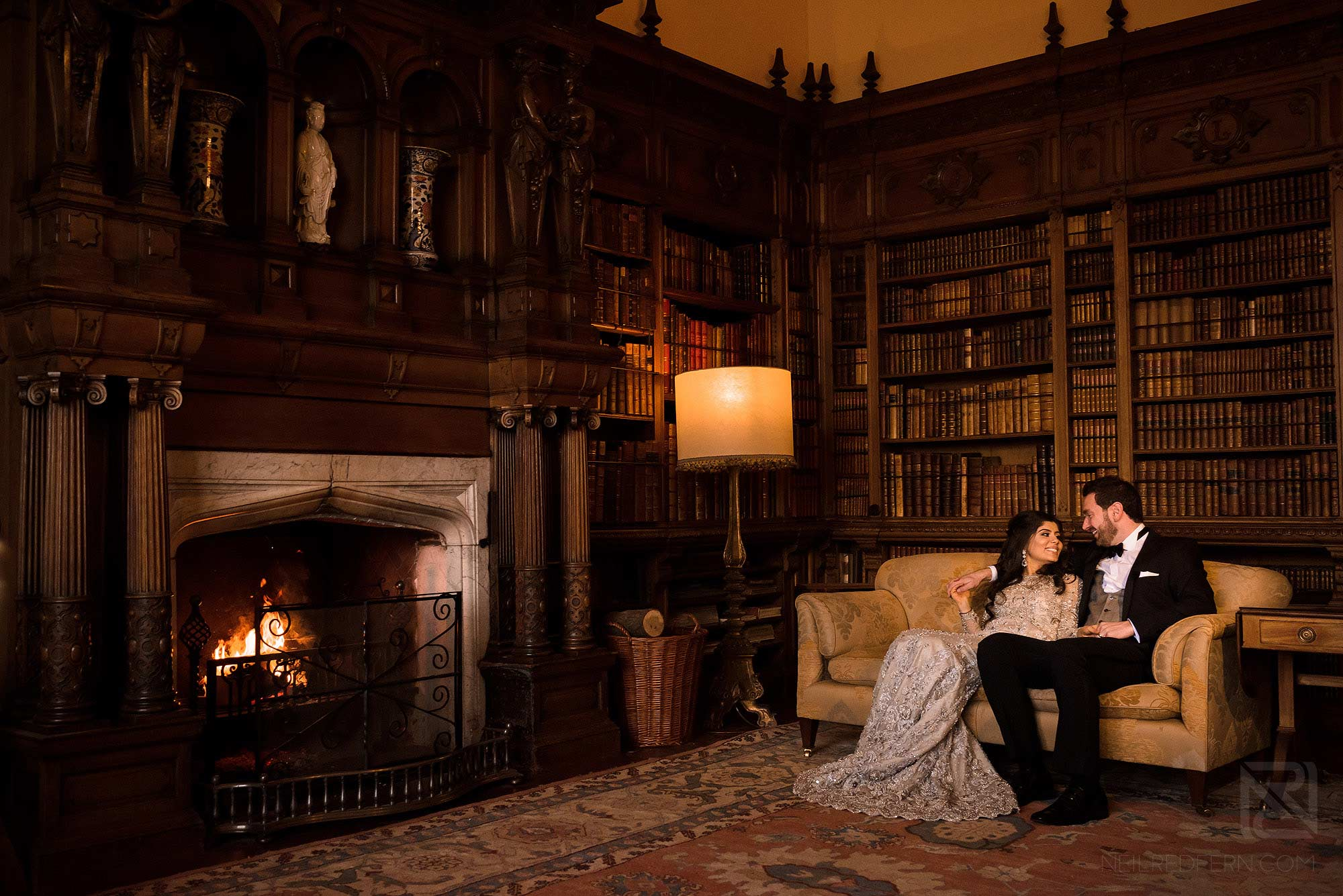 bride and couple sitting on chair in Arley Hall library