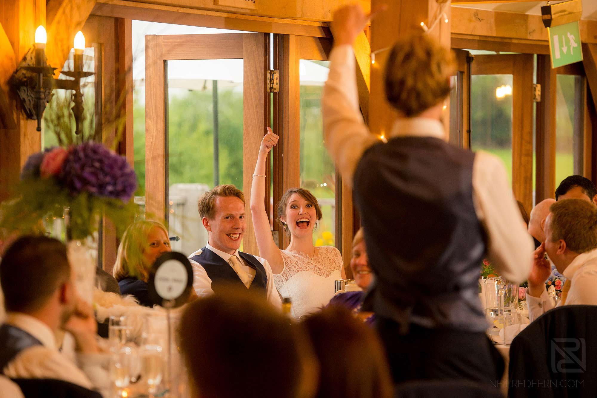 bride putting arm up laughing during wedding speeches