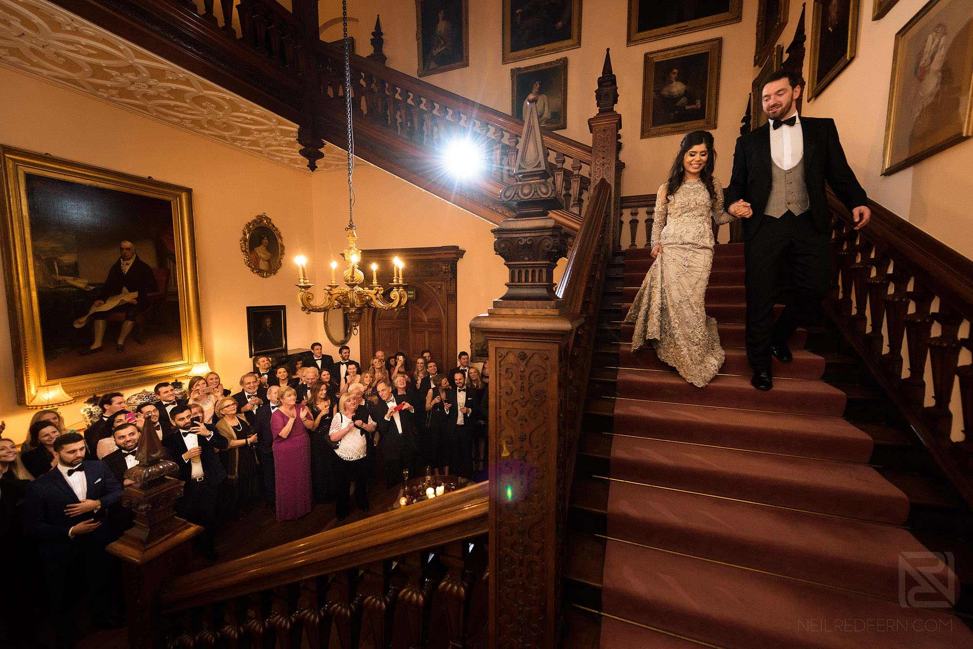 bride and groom walking down stairs at Arley Hall in front of friends and family