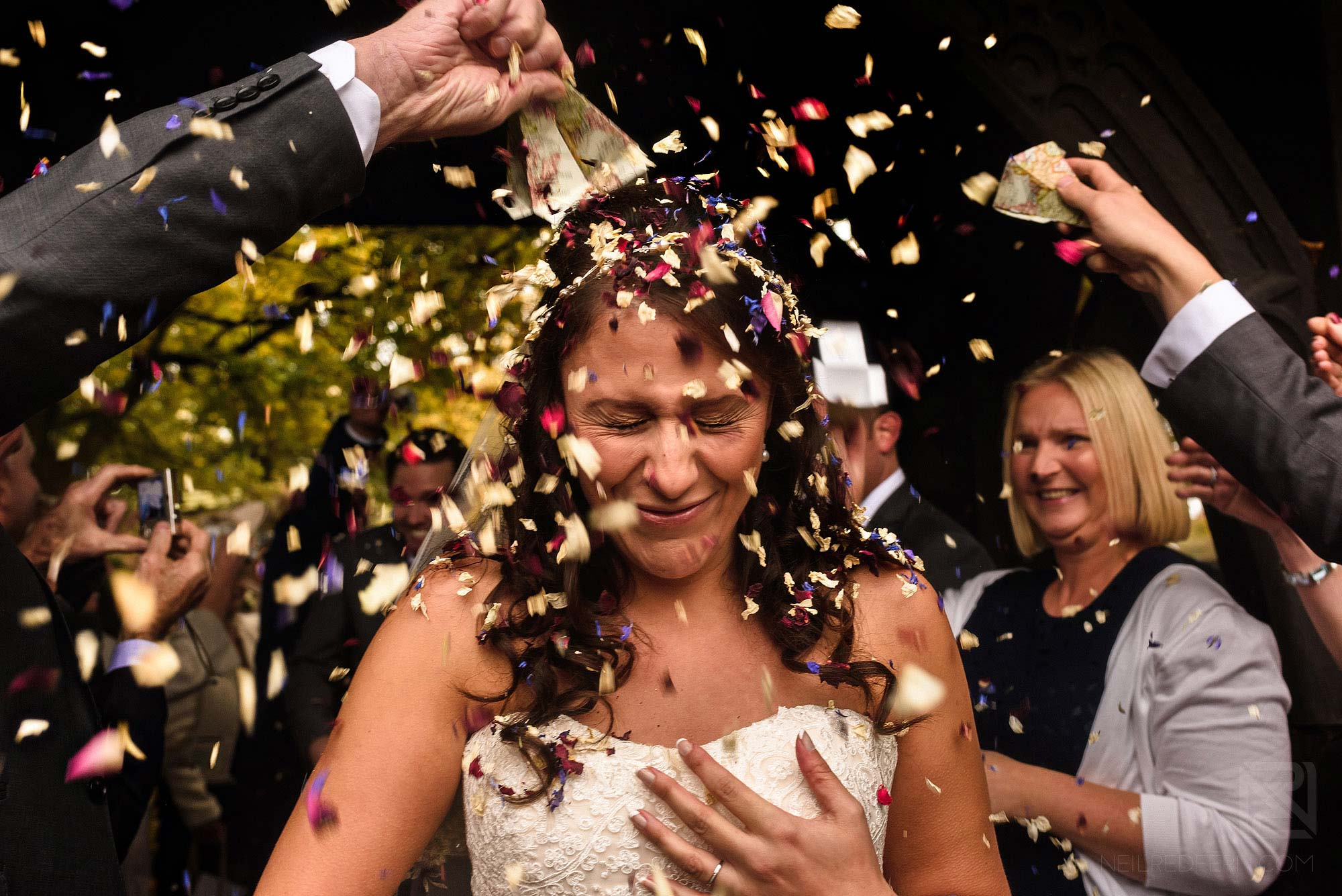 guest throwing confetti over bride outside church